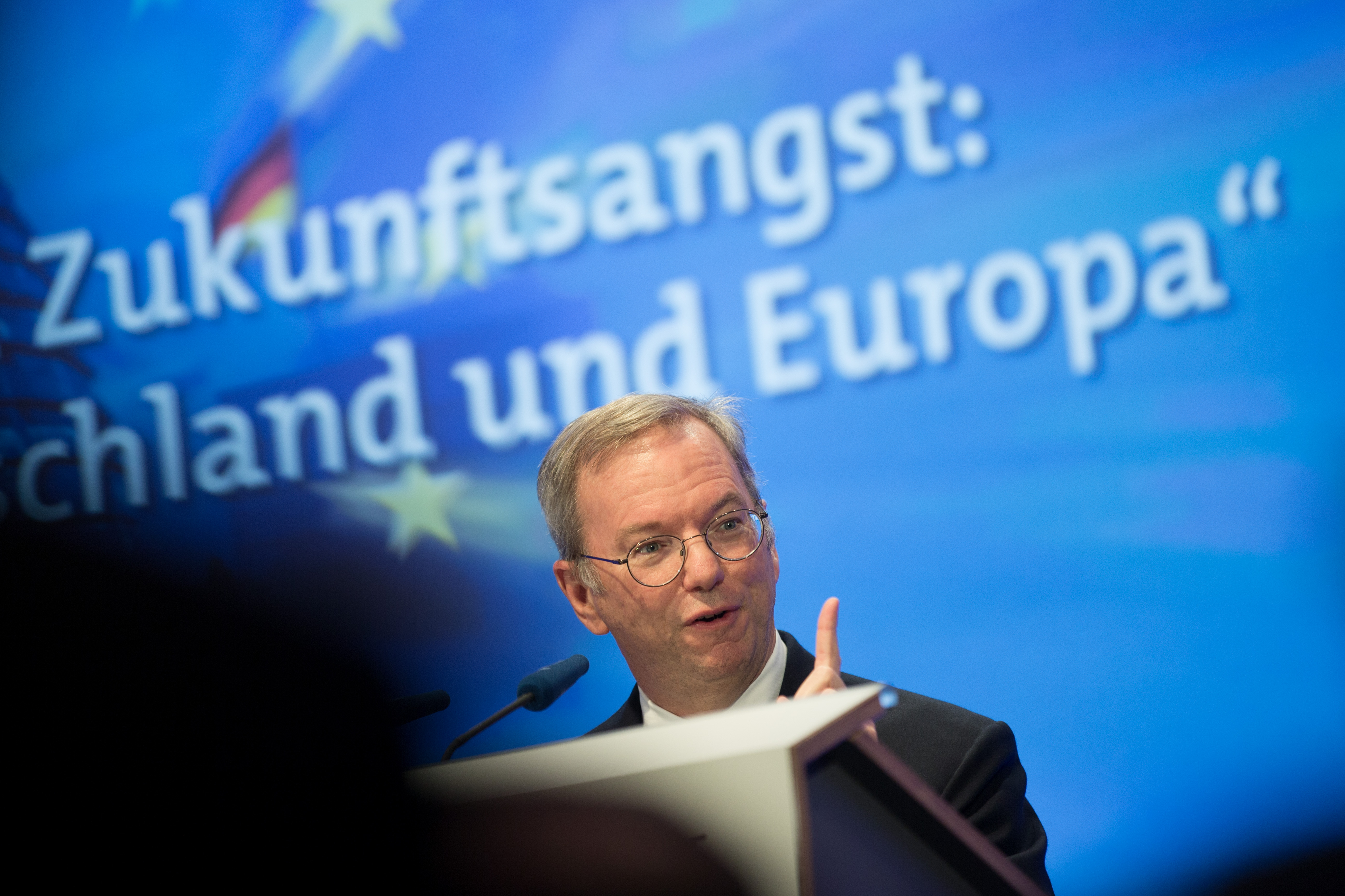 """Eric Schmidt speaks at a conference with the word """"Europa"""" behind him."""