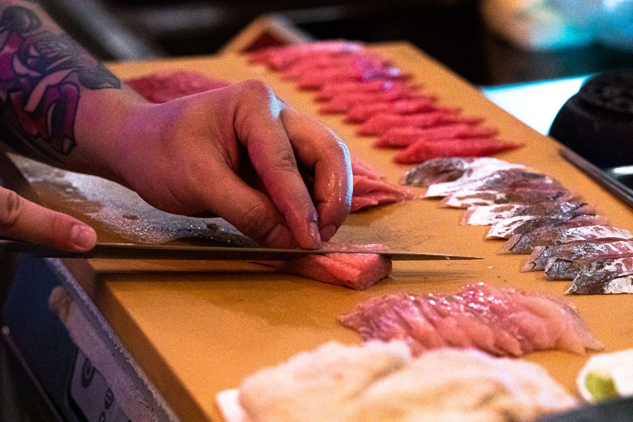 Focus on hands slicing sushi with several slices already laid out on a wooden board