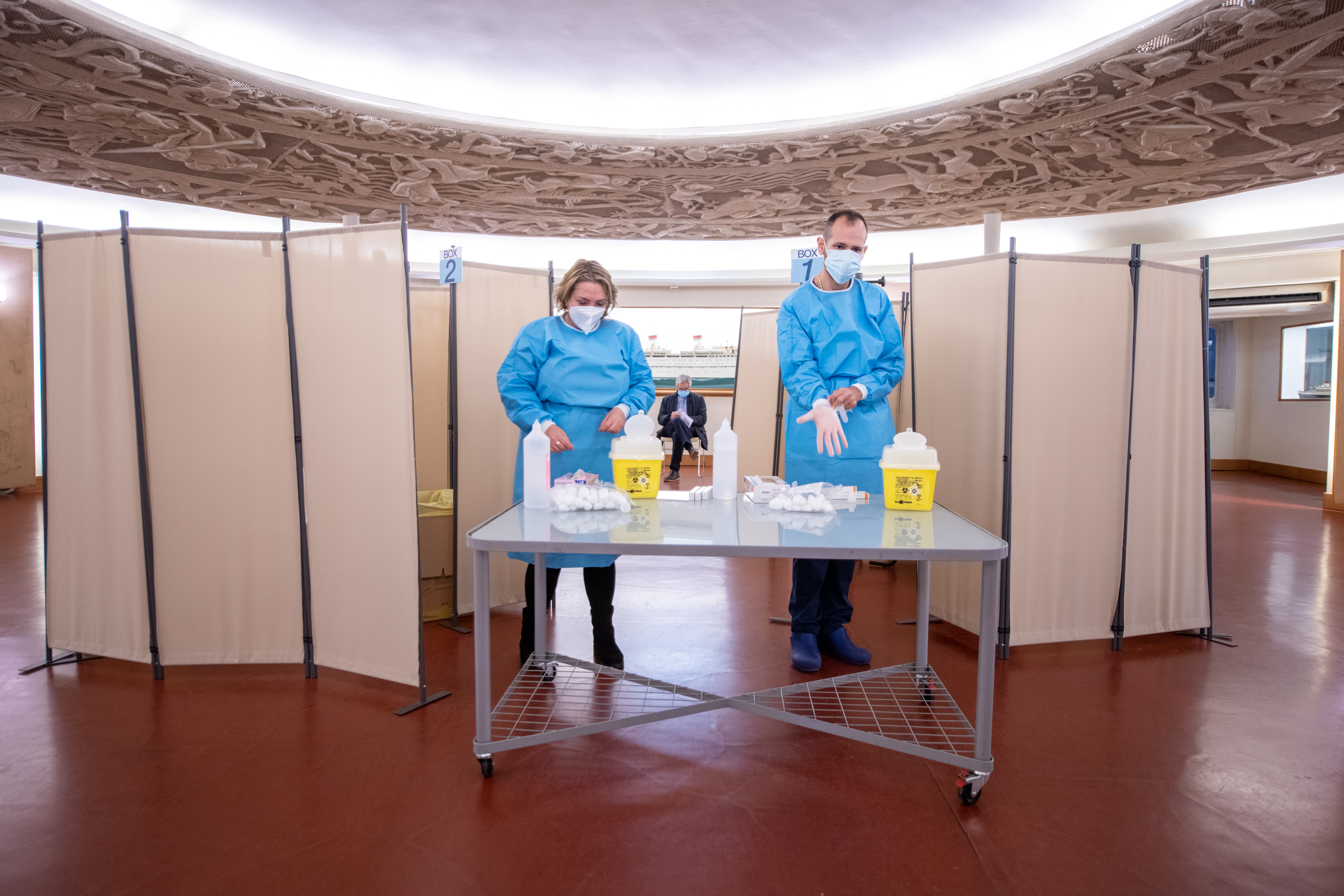 Two people stand at a table in protective gowns, gloves, and masks in preparation for distribution of a flu vaccine.