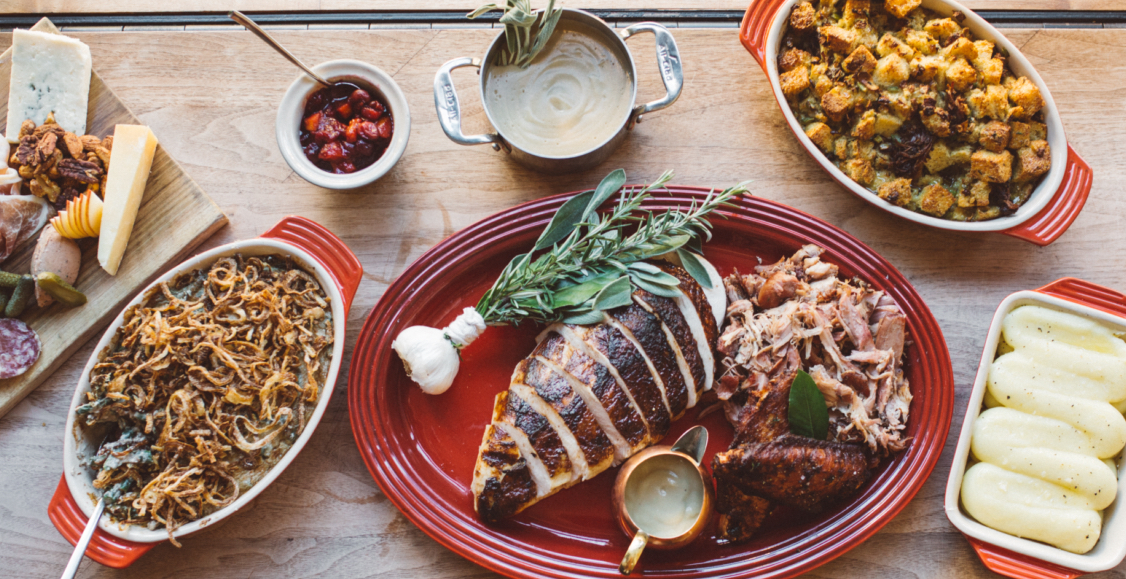 On a butcher block background is a full Thanksgiving feast with roast turkey breast, green bean casserole, whipped mashed potatoes in an orange Le Cruset pan, and a charcuterie board