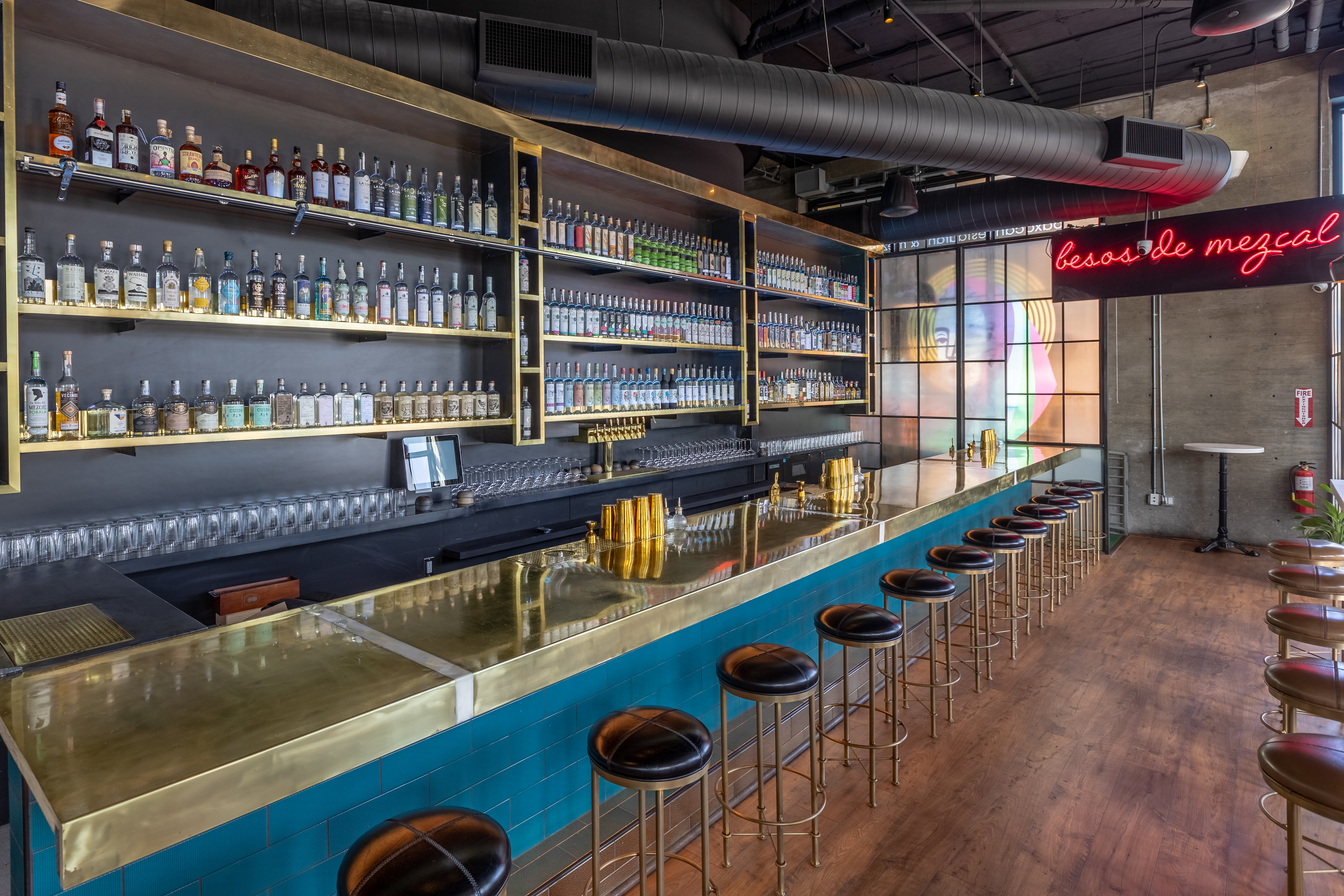 """The bar and counter at Madre West Hollywood with bottles and neon sign reading """"besos de mezcal""""."""