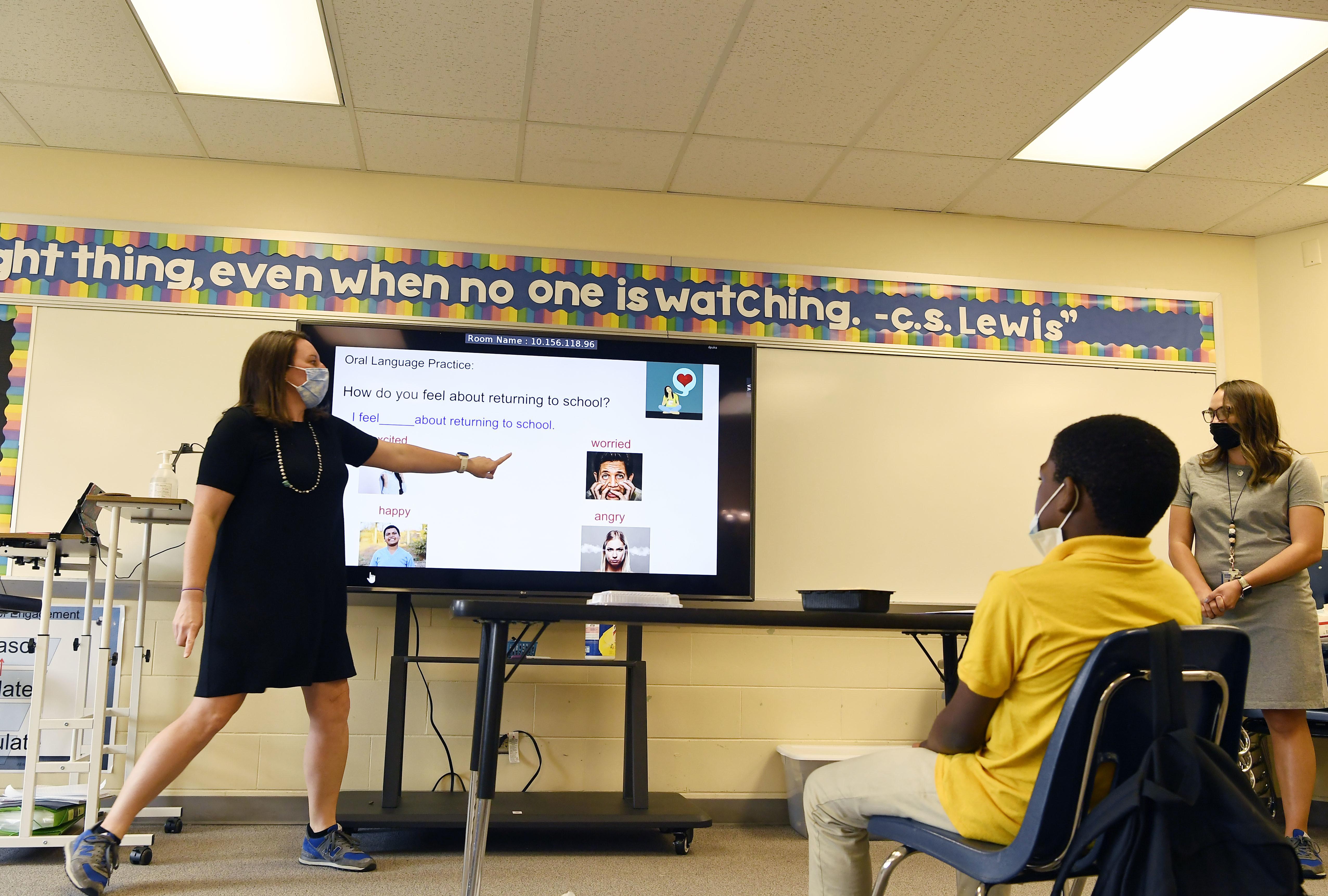 An Aurora teacher wearing a mask points at a screen as students watch.