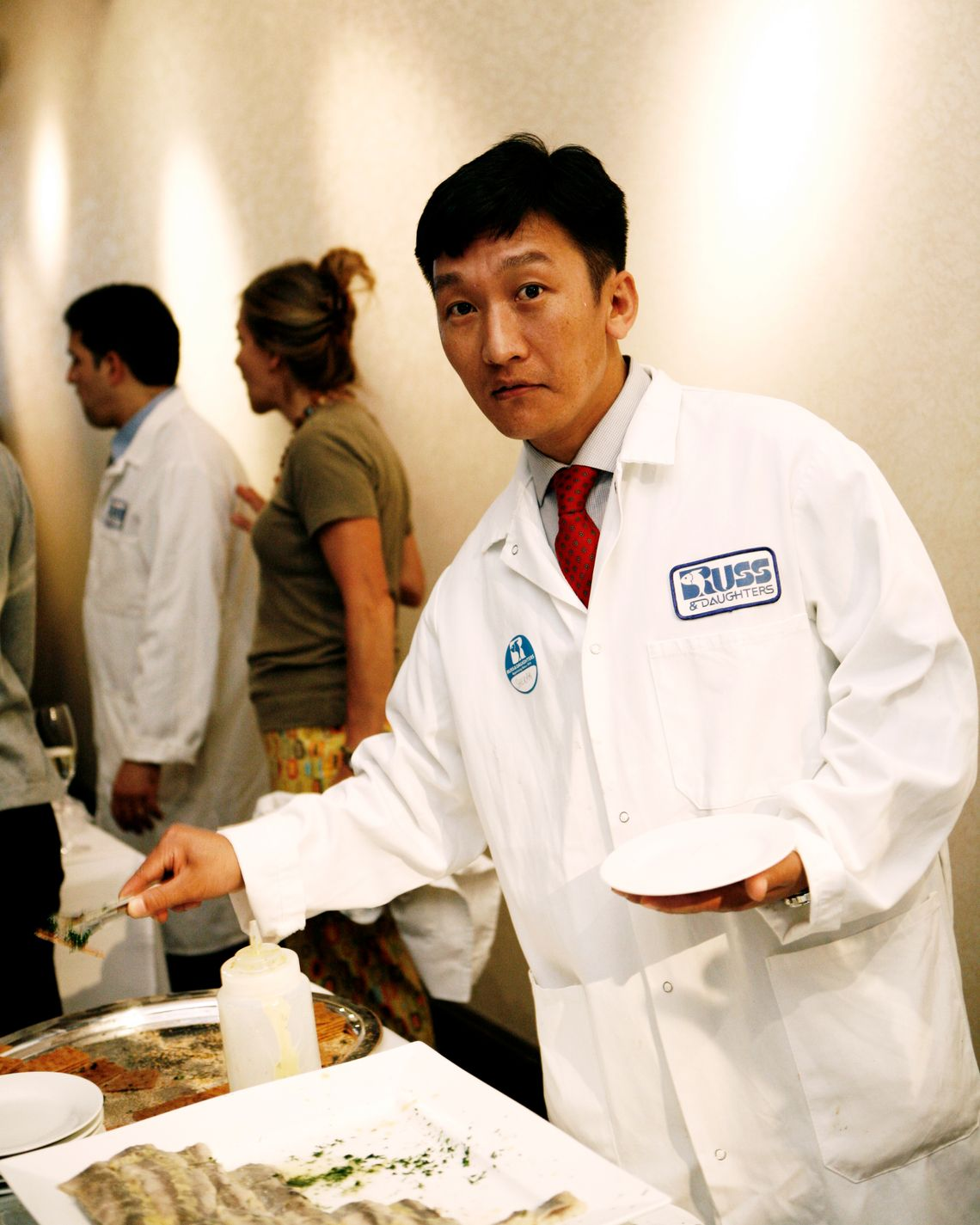 A man stands in a white coat looking into the camera, while he reaches with a utensil to scoop smoked fish