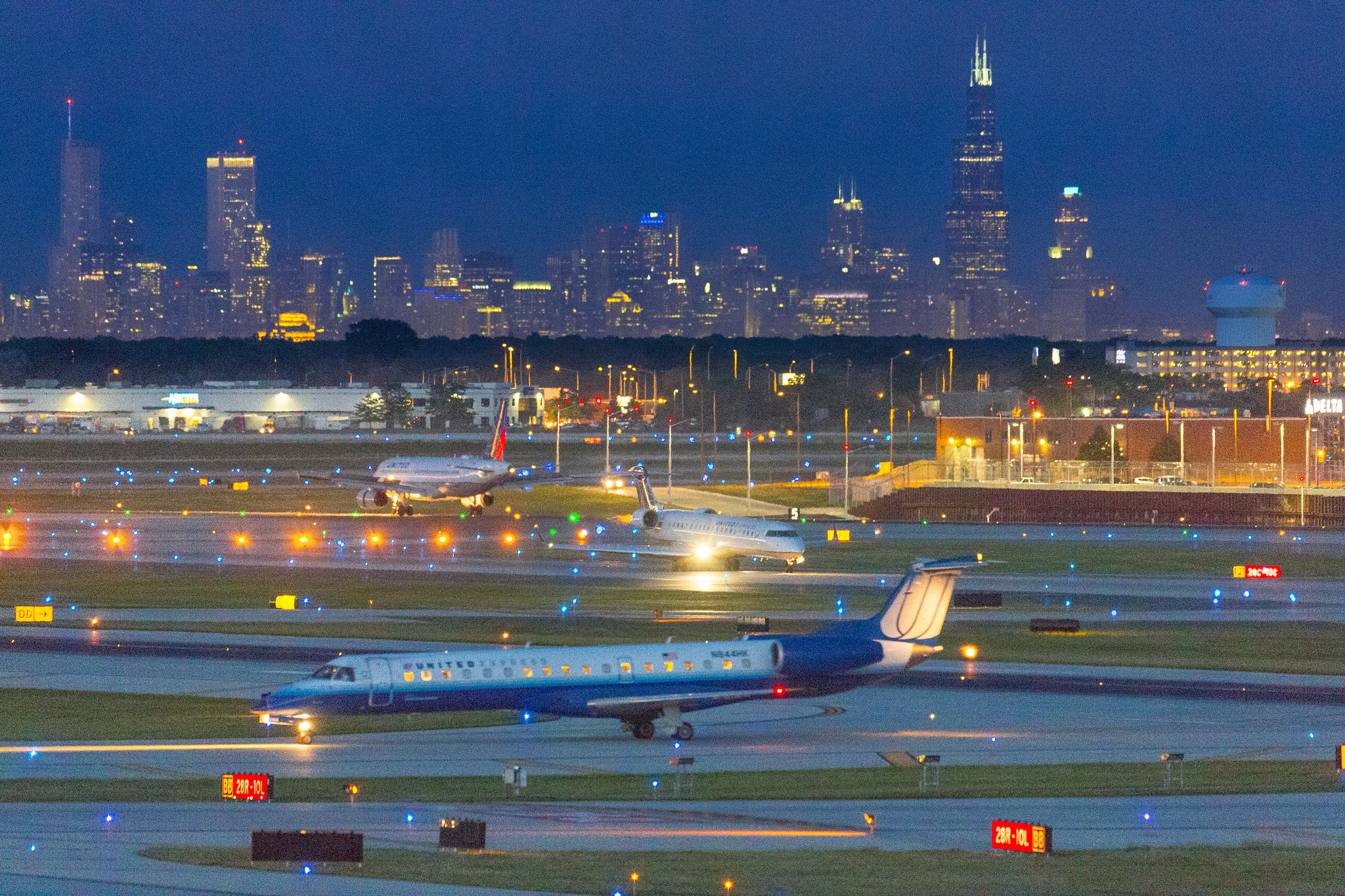 An airfield lit up at night with Chicago's skyline in the background.
