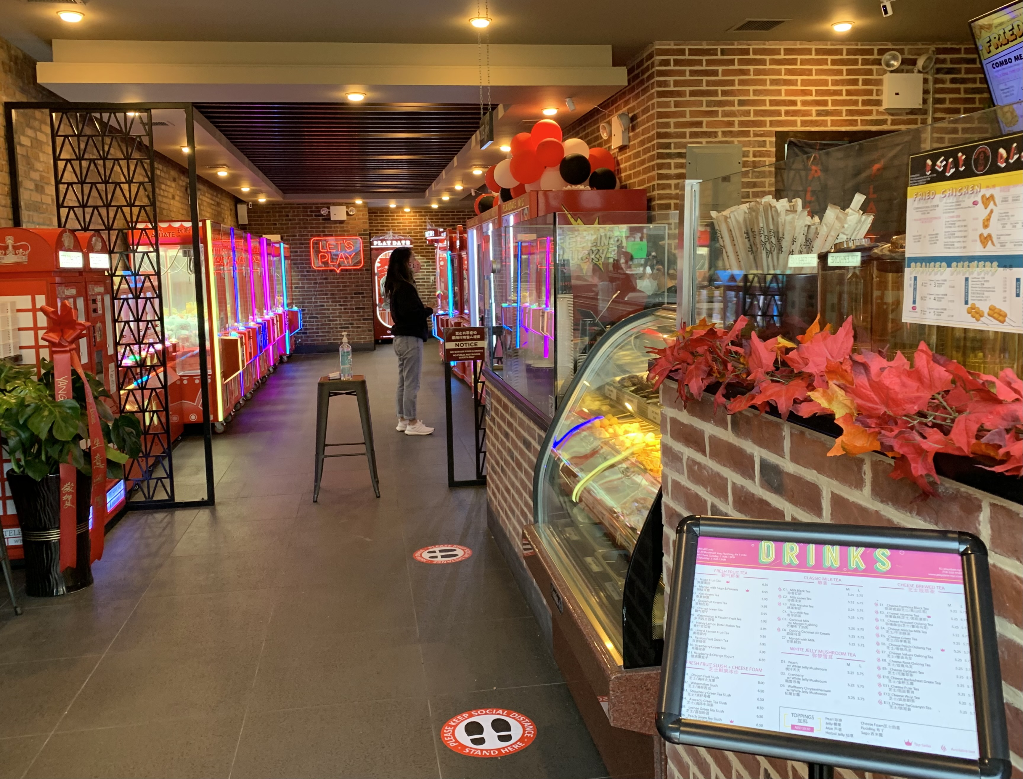 Inside a restaurant where an ordering counter can be seen in the front and a row of arcade games in the back
