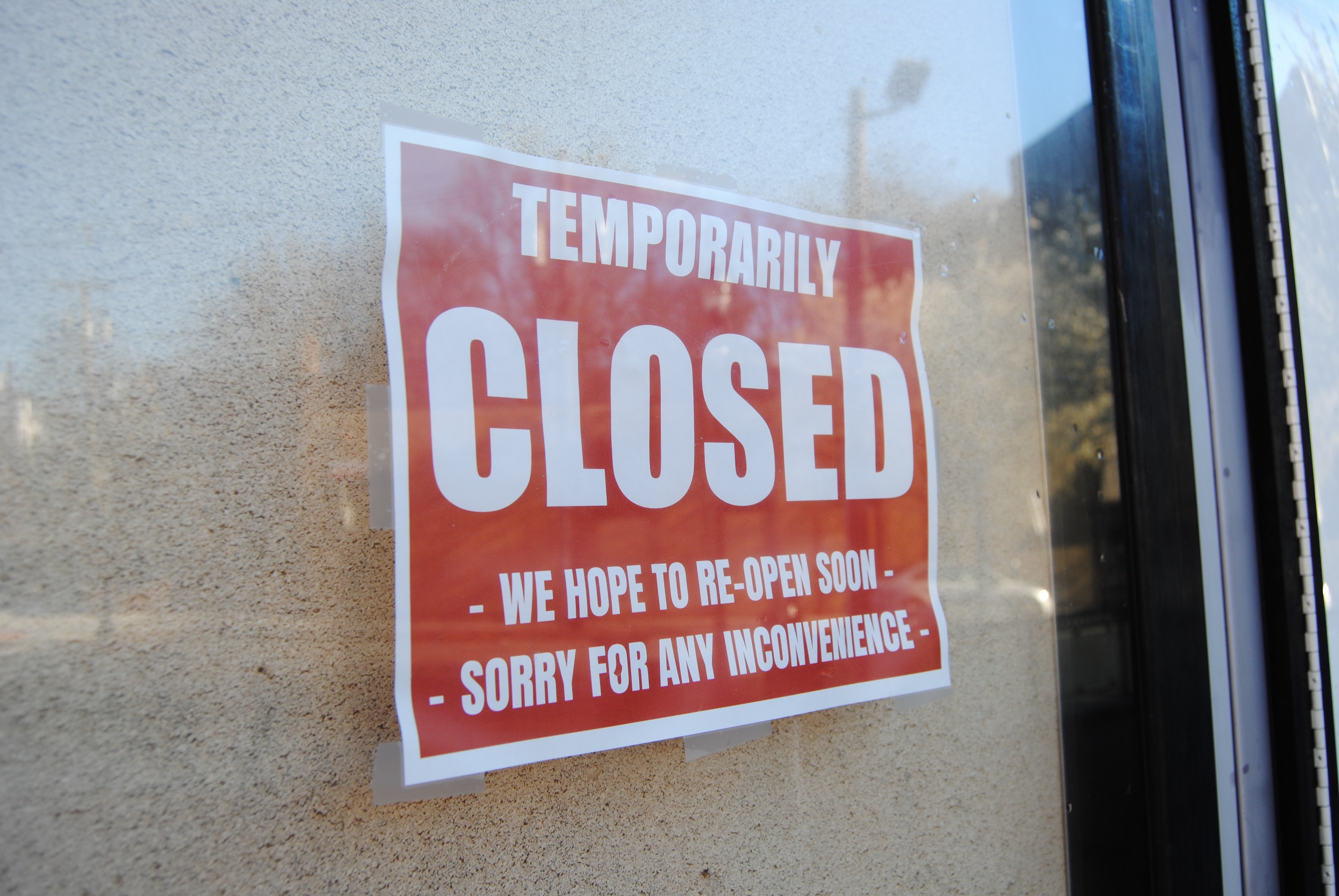 A red sign in a window states that the business is temporarily closed.