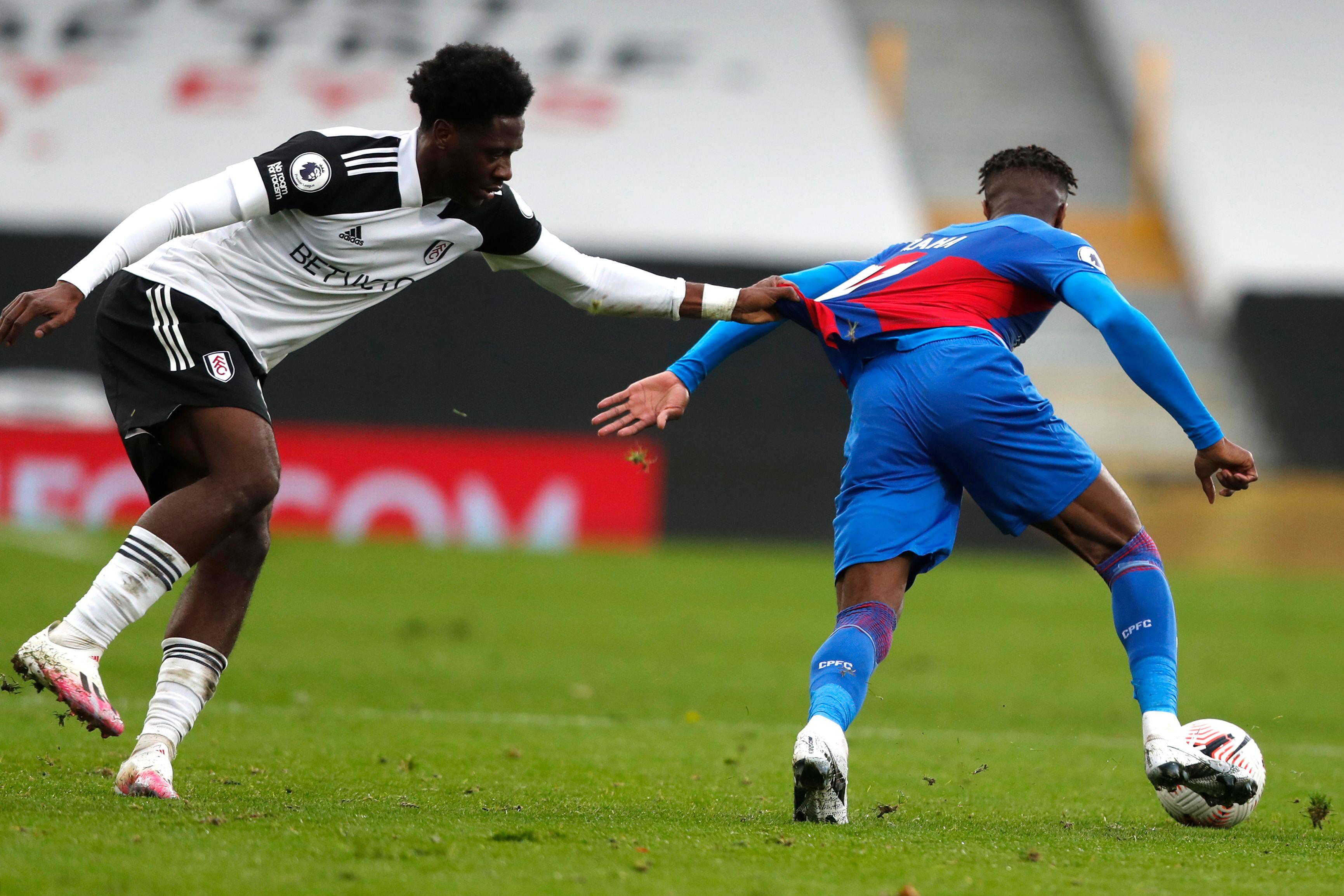 Nigerian defender Ola Aina pulls the shirt of Ivorian striker Wilfried Zaha - Fulham vs Crystal Palace - Premier League