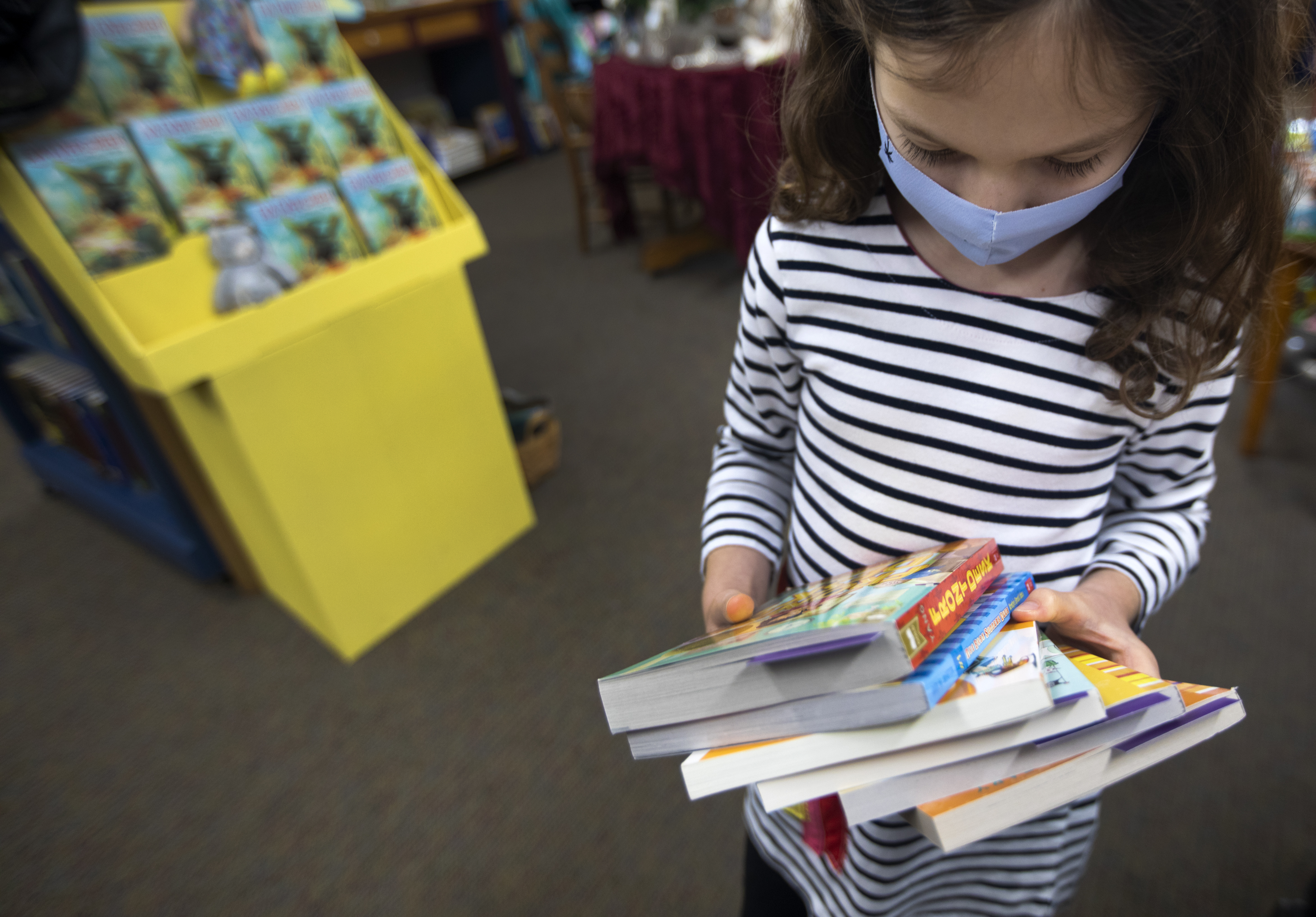 A masked child looks at her armful of books she holds inside the Once Upon a Time bookstore in Montrose.