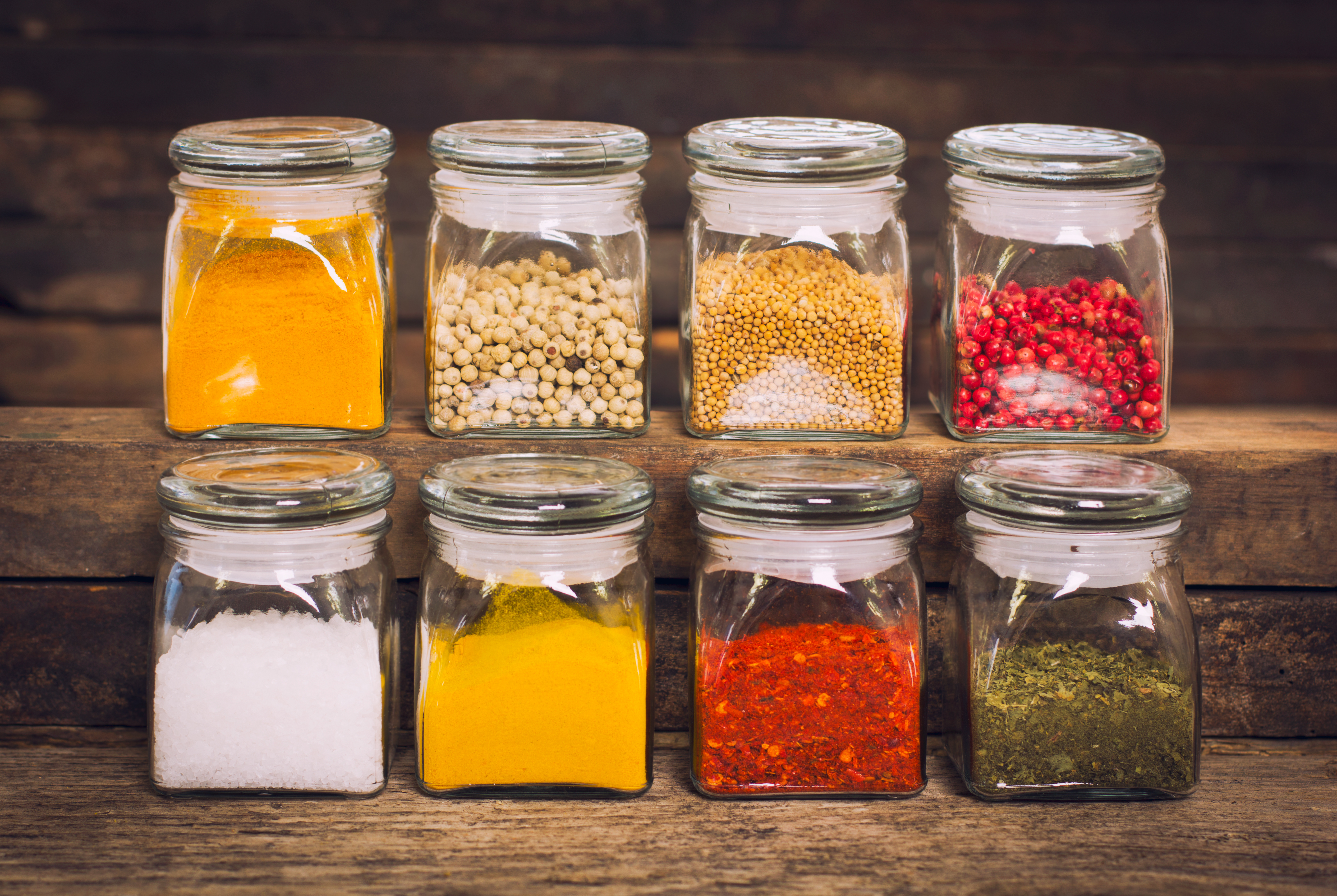 Two rows of spices in glass containers on a wooden shelf