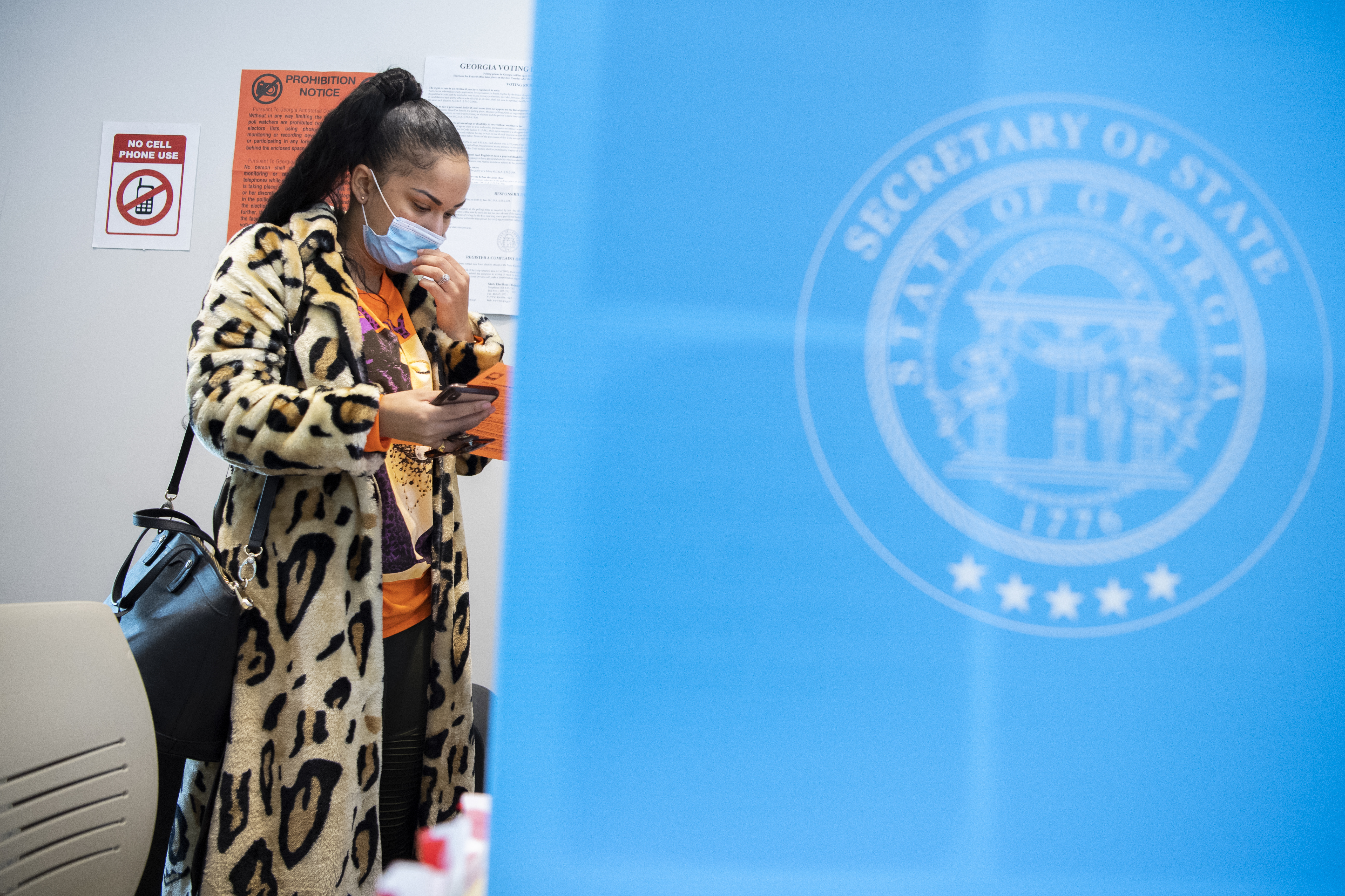 A woman stands in line, waiting to vote. She's looking at her phone.