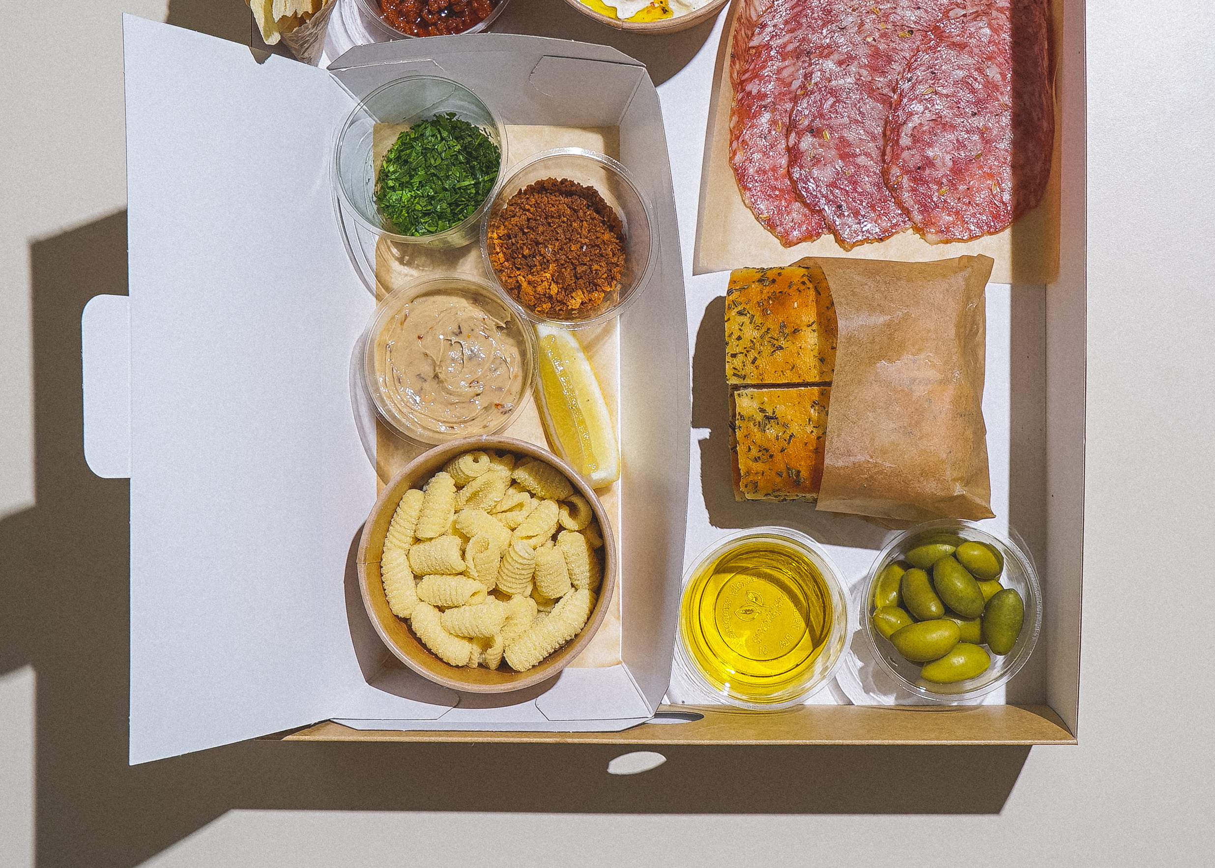 Fresh pasta, sauce, salumi, foccaccia, and olives in a cardboard meal kit box, shot from a birdseye view