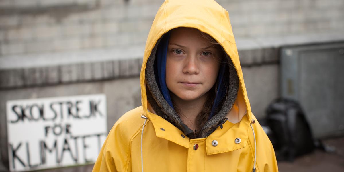 Greta Thunberg stands in a yellow rain slicker.