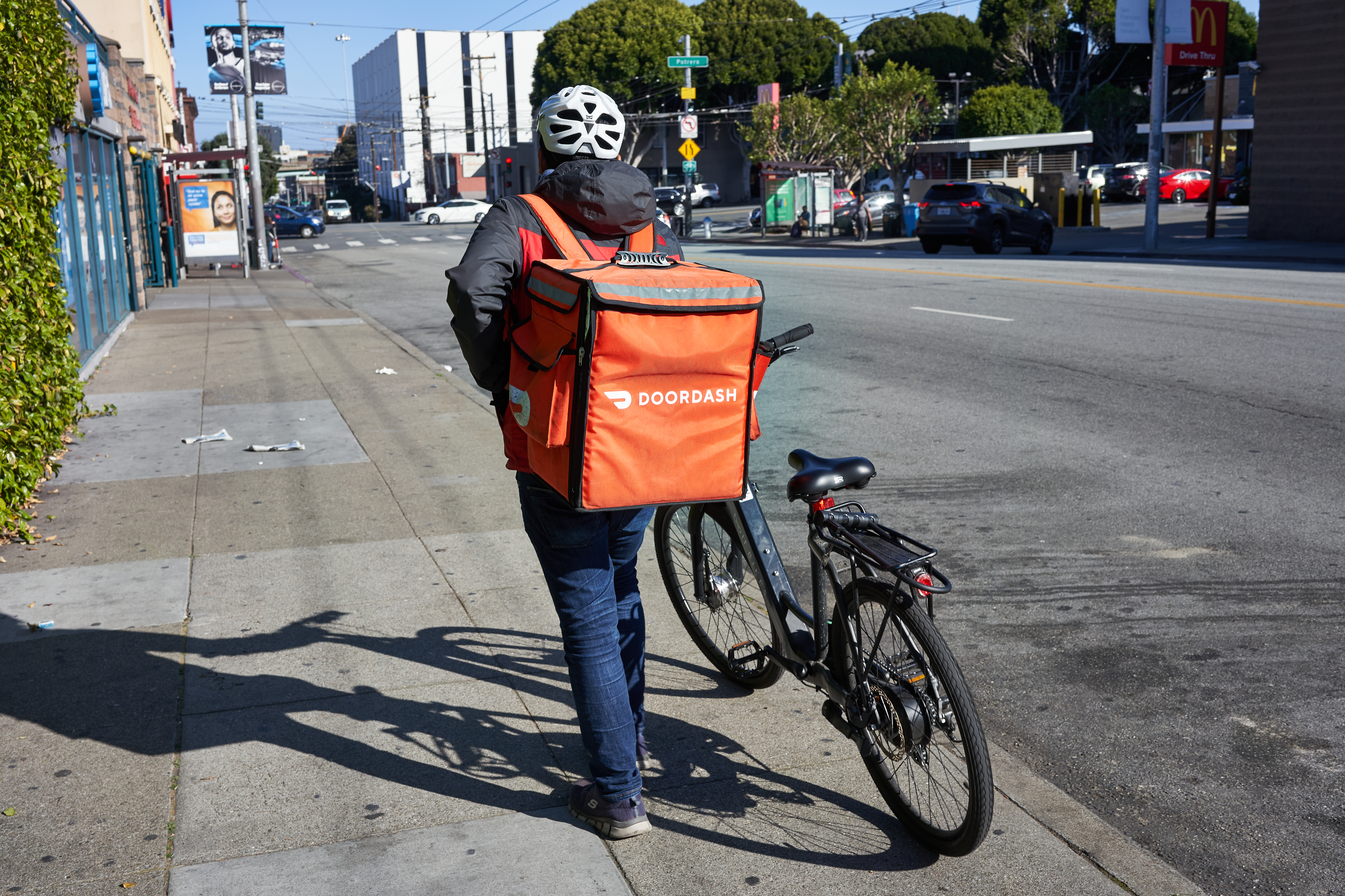 A DoorDash delivery worker walks his bike along the road in the Mission neighborhood of San Francisco, California.