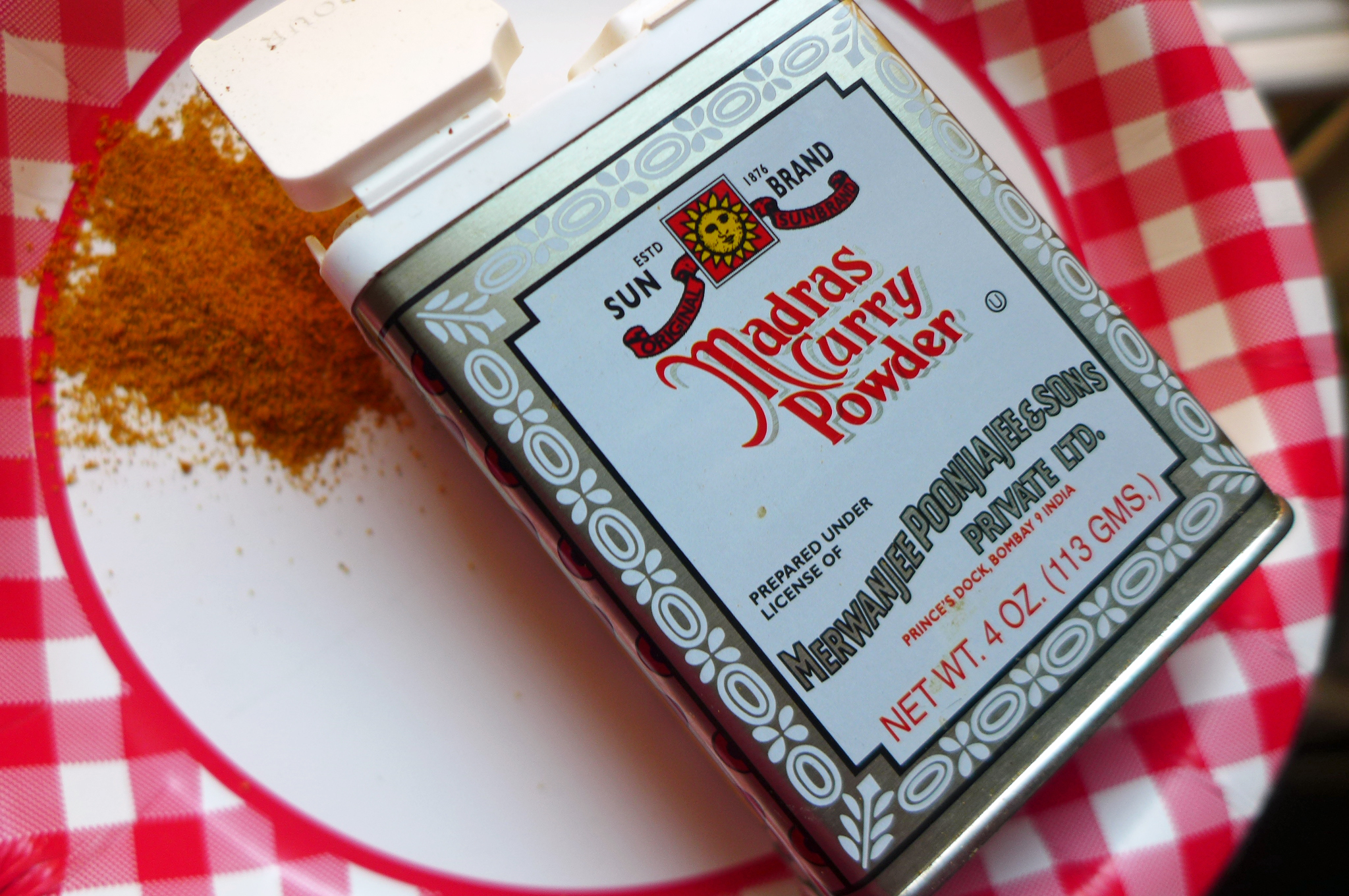 A rectangular tin of with ornate lettering and curry powder spilling out the top.