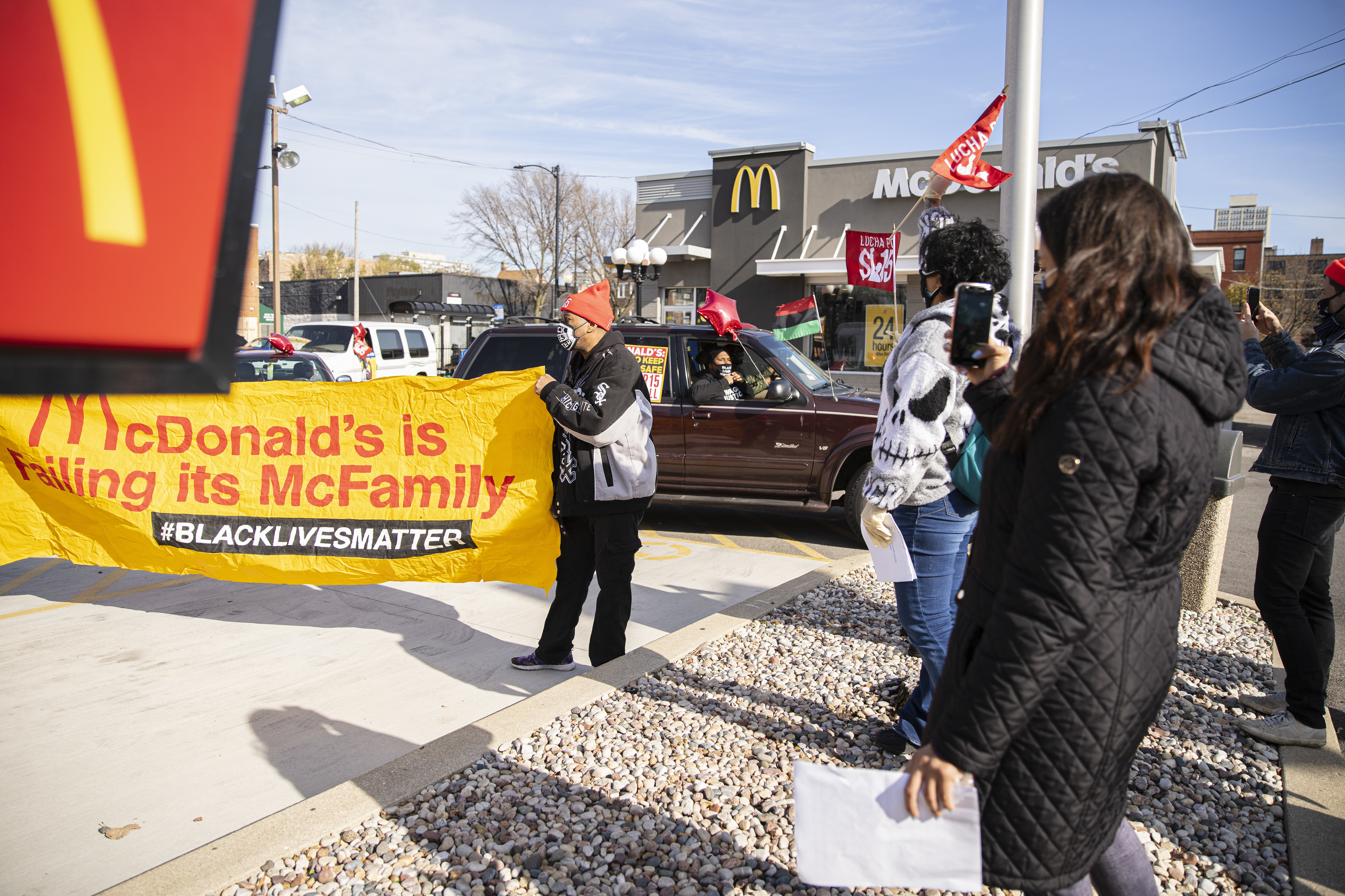 Protesters hold banners and ride around in a caravan Thursday outside McDonald's at 207 E. 35th St. in Bronzeville.