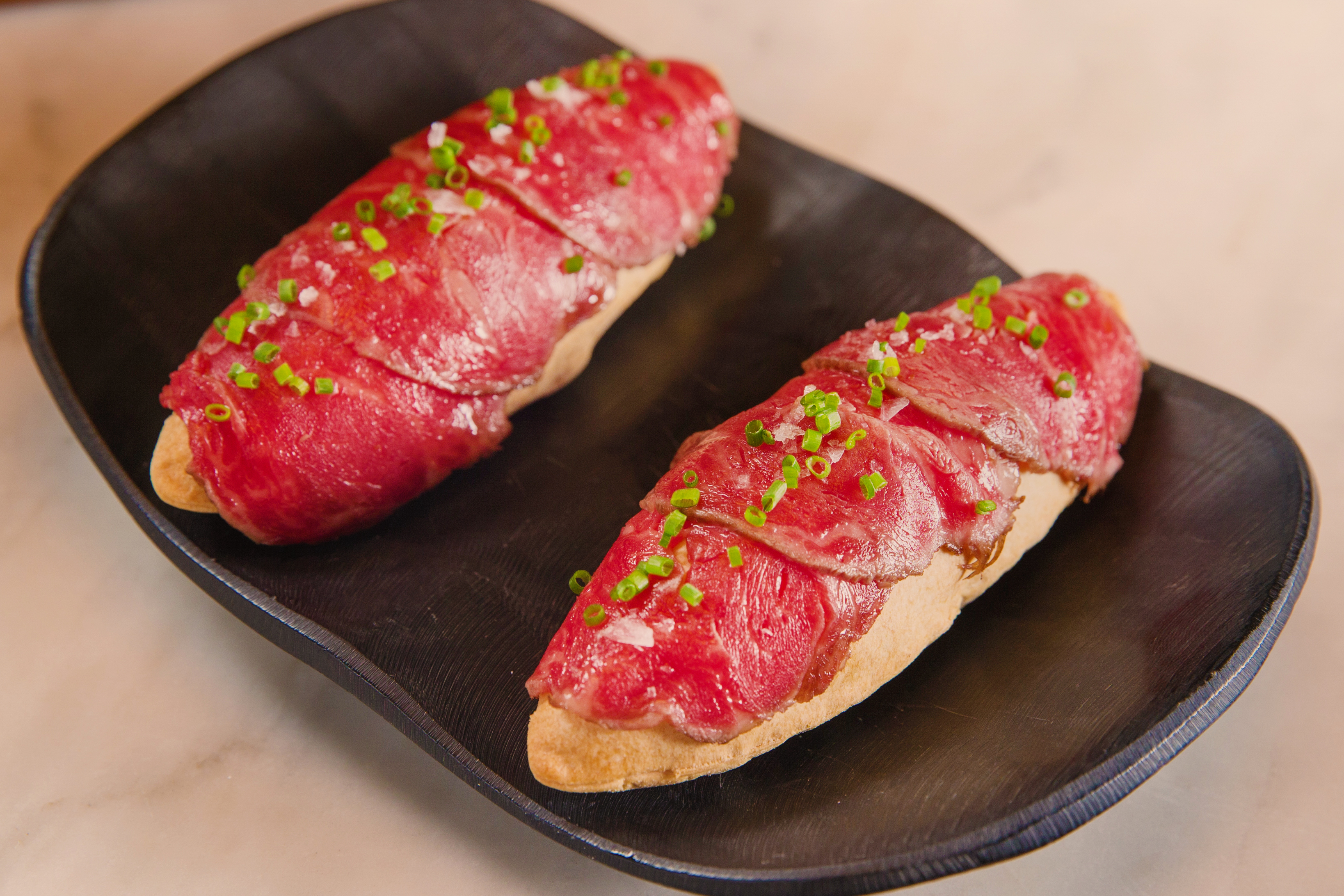 Two rolls with thinly sliced meat on top