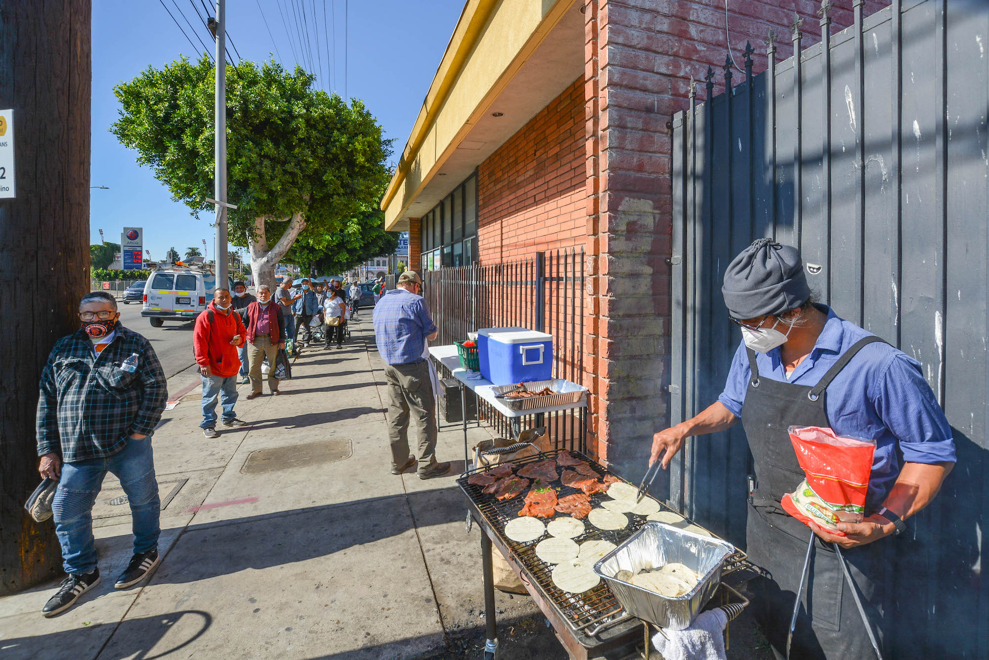 A man in a beanie turns food on a grill at a free community food giveaway.