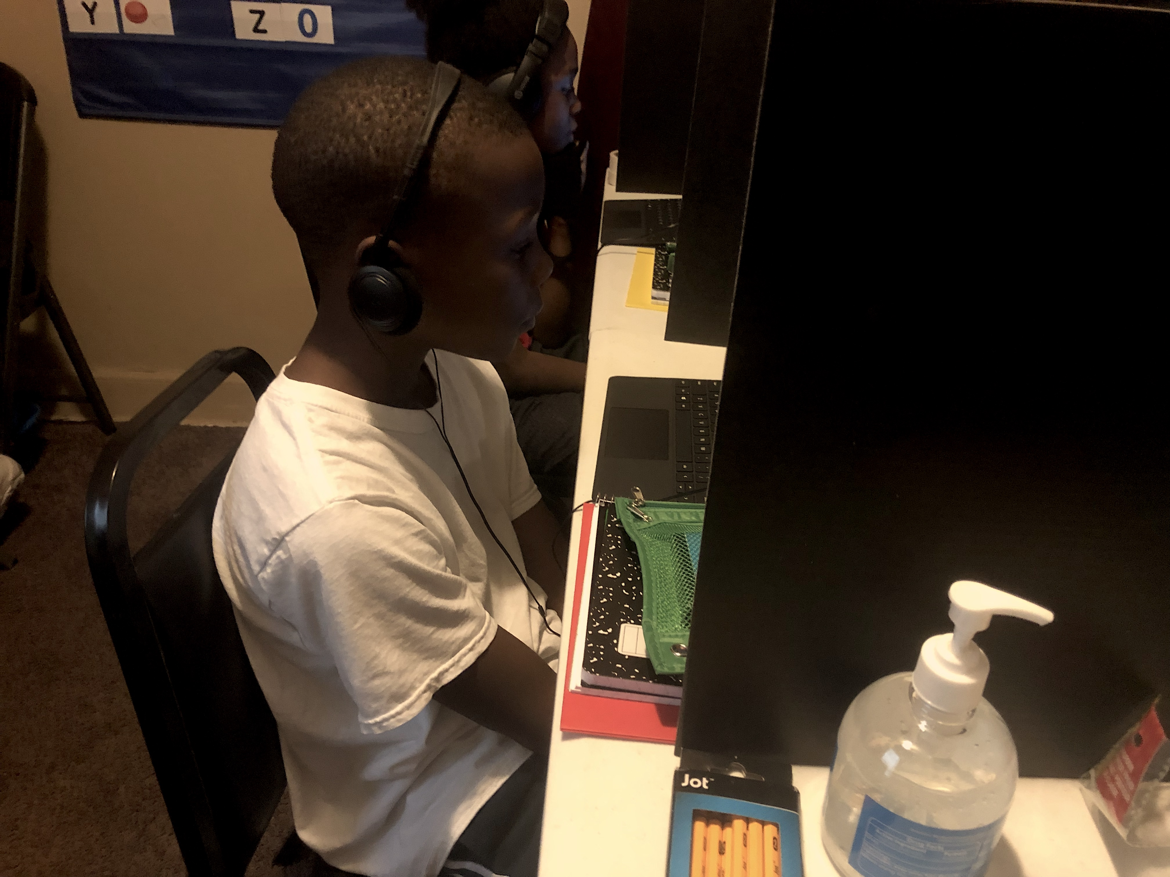 A third-grade student sits at a desk in front of a laptop with his hands in his lap as he listens to an online class.