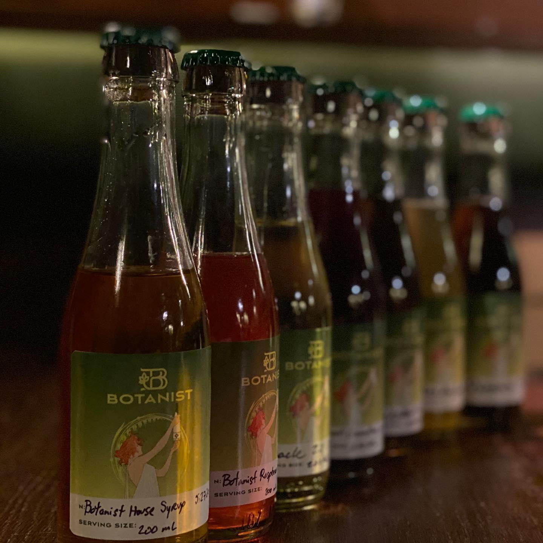 A line of wine-based cocktails sit on a bar at Botanist