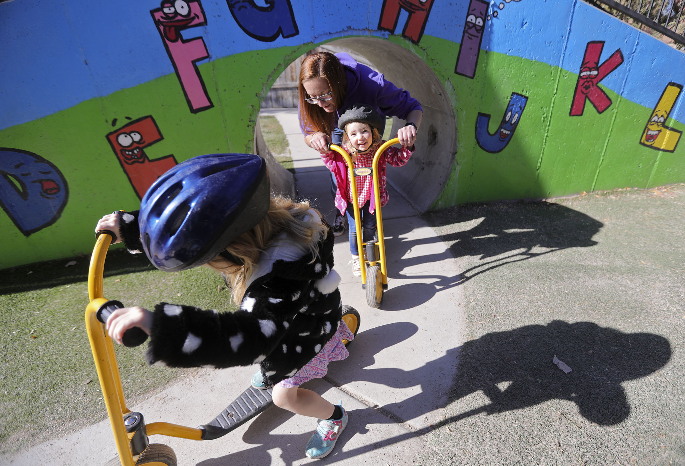Preschool teacher Jenna Berkey pushes Avery Black on a scooter at A to Z Building Blocks, a child care and preschool facility, in American Fork on Thursday, Nov. 5, 2020.