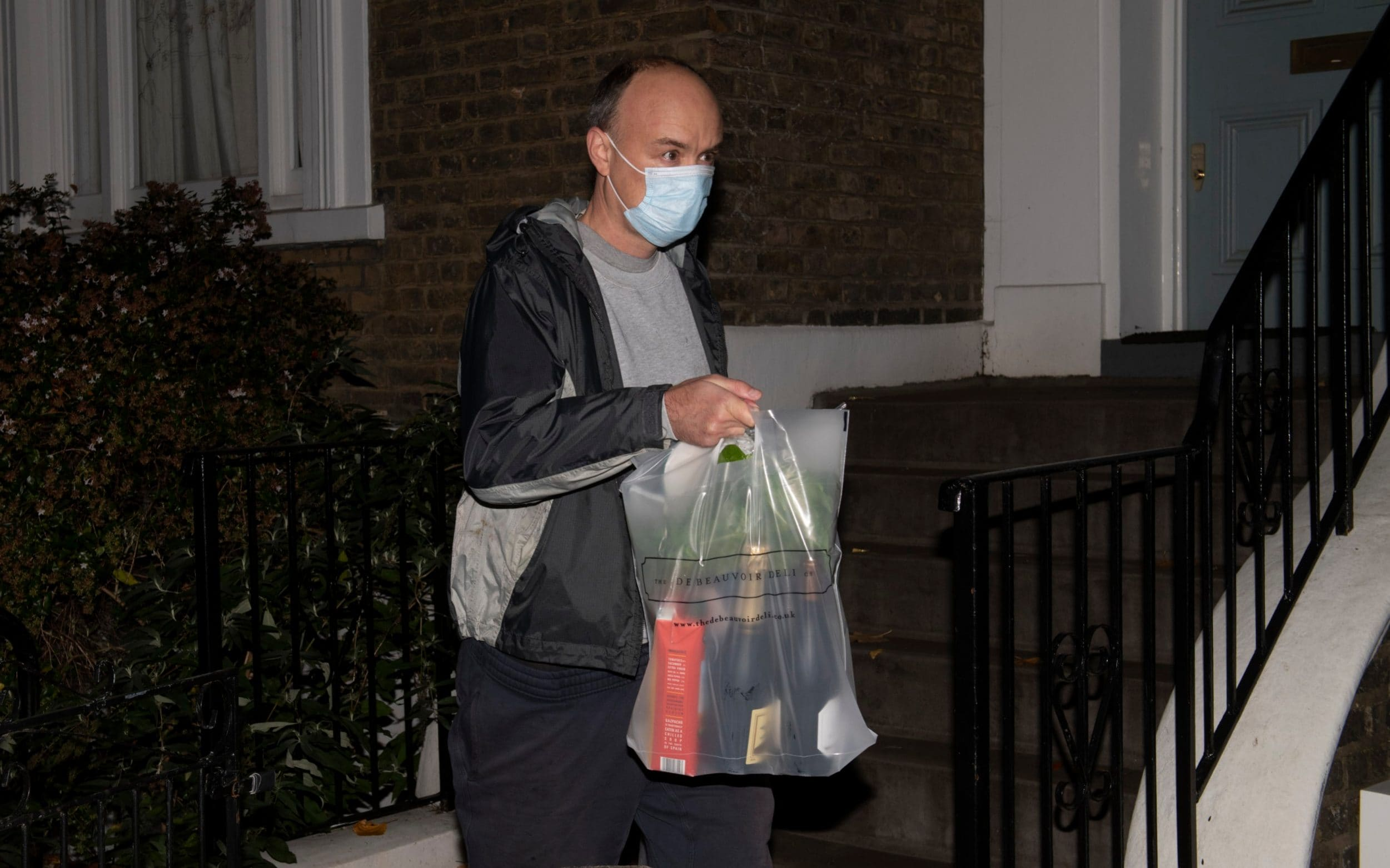 Dominic Cummings wears a mask as he walks down a street carrying a plastic bag full of champagne, wine, and gazpacho