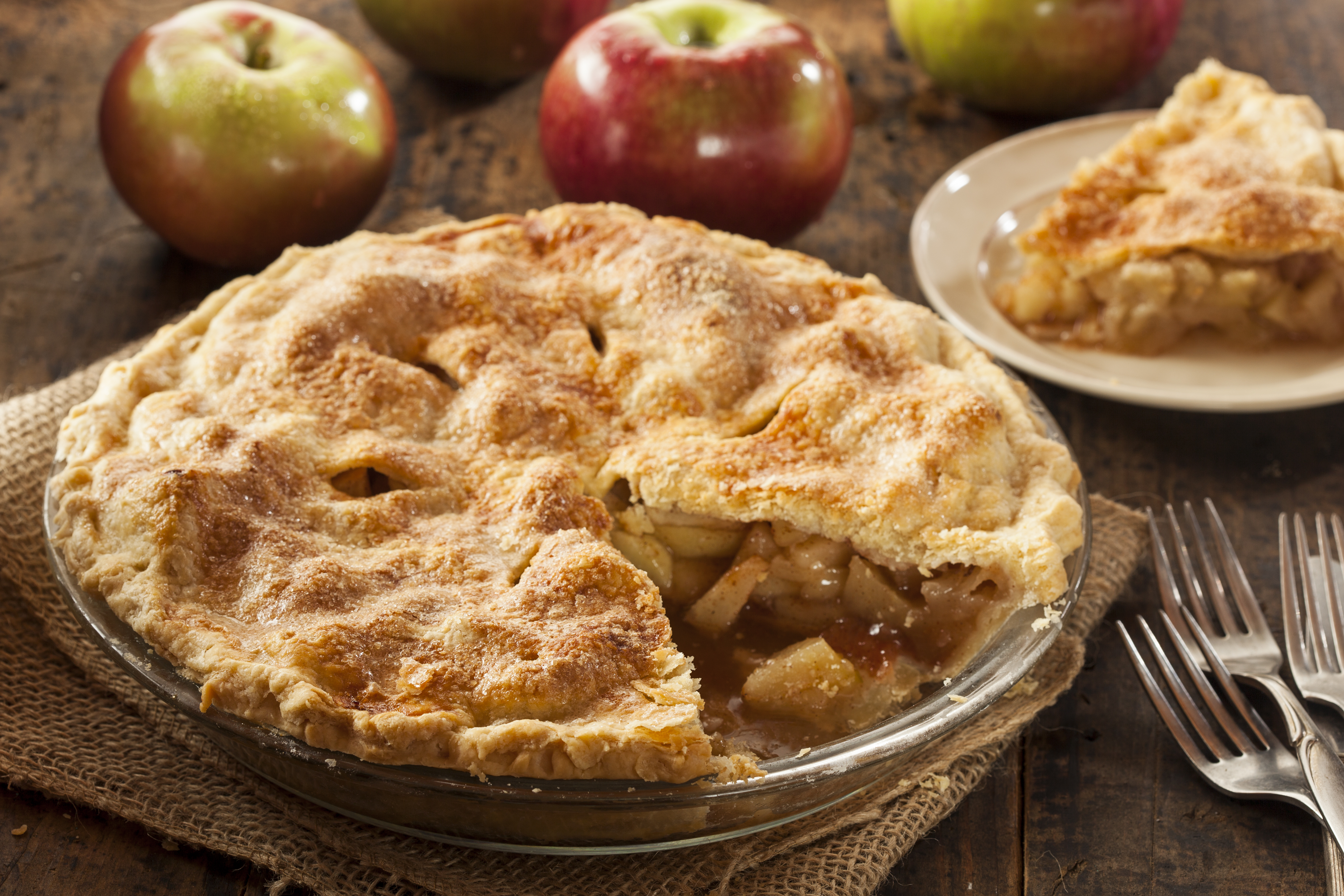 In this stock photograph, an apple pie sits on a table with a slice cut out of it; the slice is on a small white plate in the background. Several forks are on the table, as are apples.