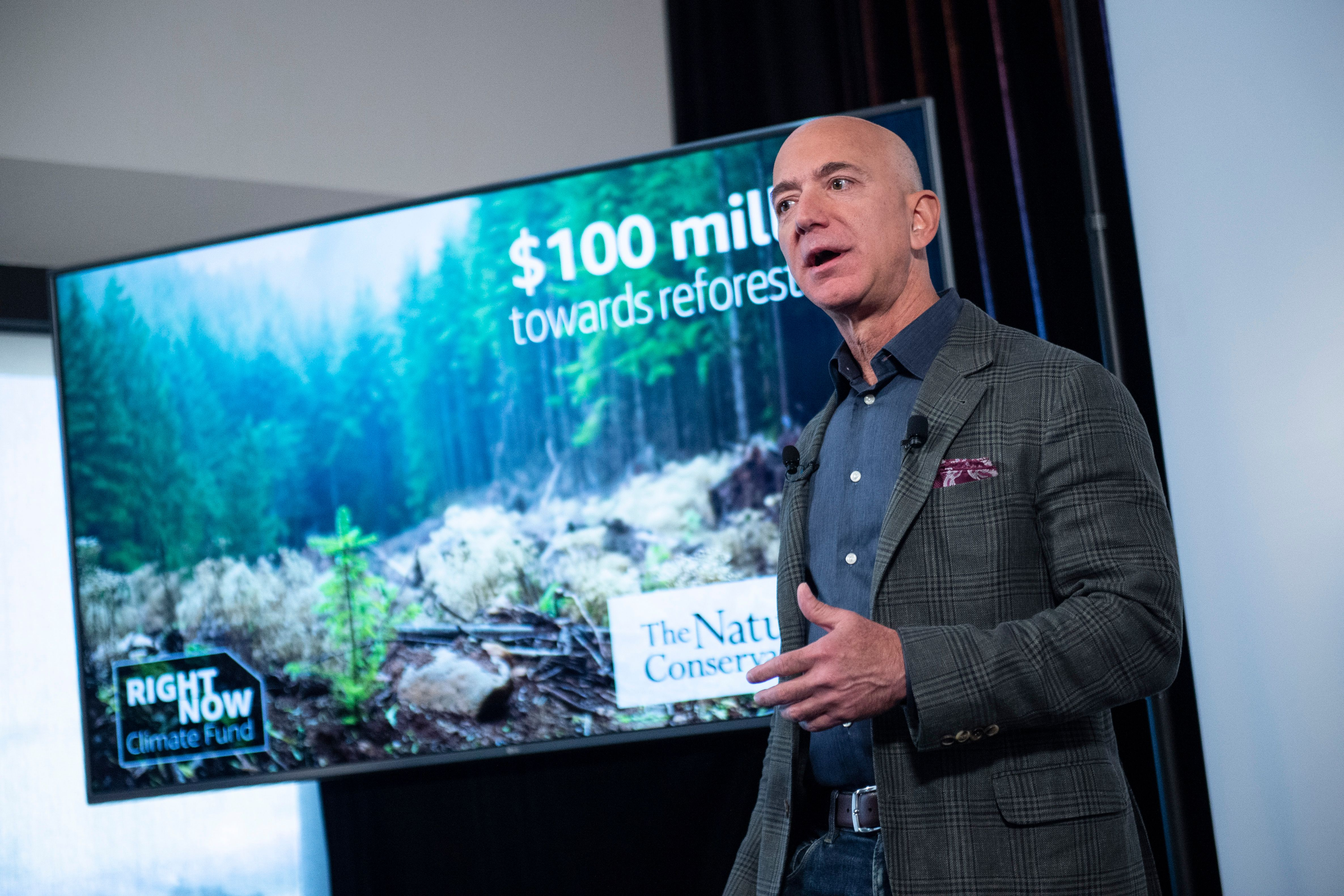 """Amazon founder Jeff Bezos speaks onstage in front of a screen showing a wooded landscape and the words """"$100 million."""""""