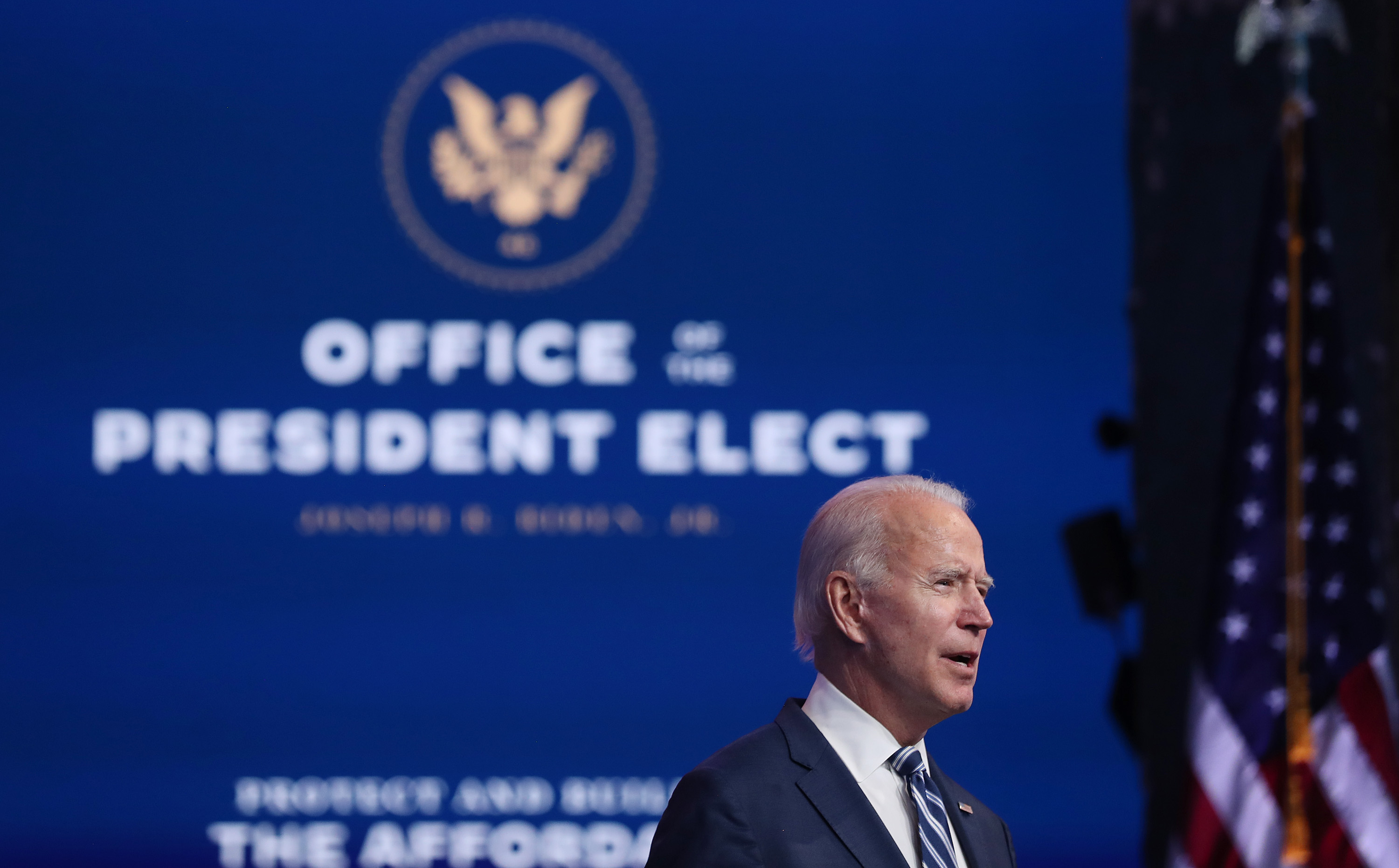 """Joe Biden speaks at a podium in front of a backdrop reading, """"Office of the President-elect"""""""