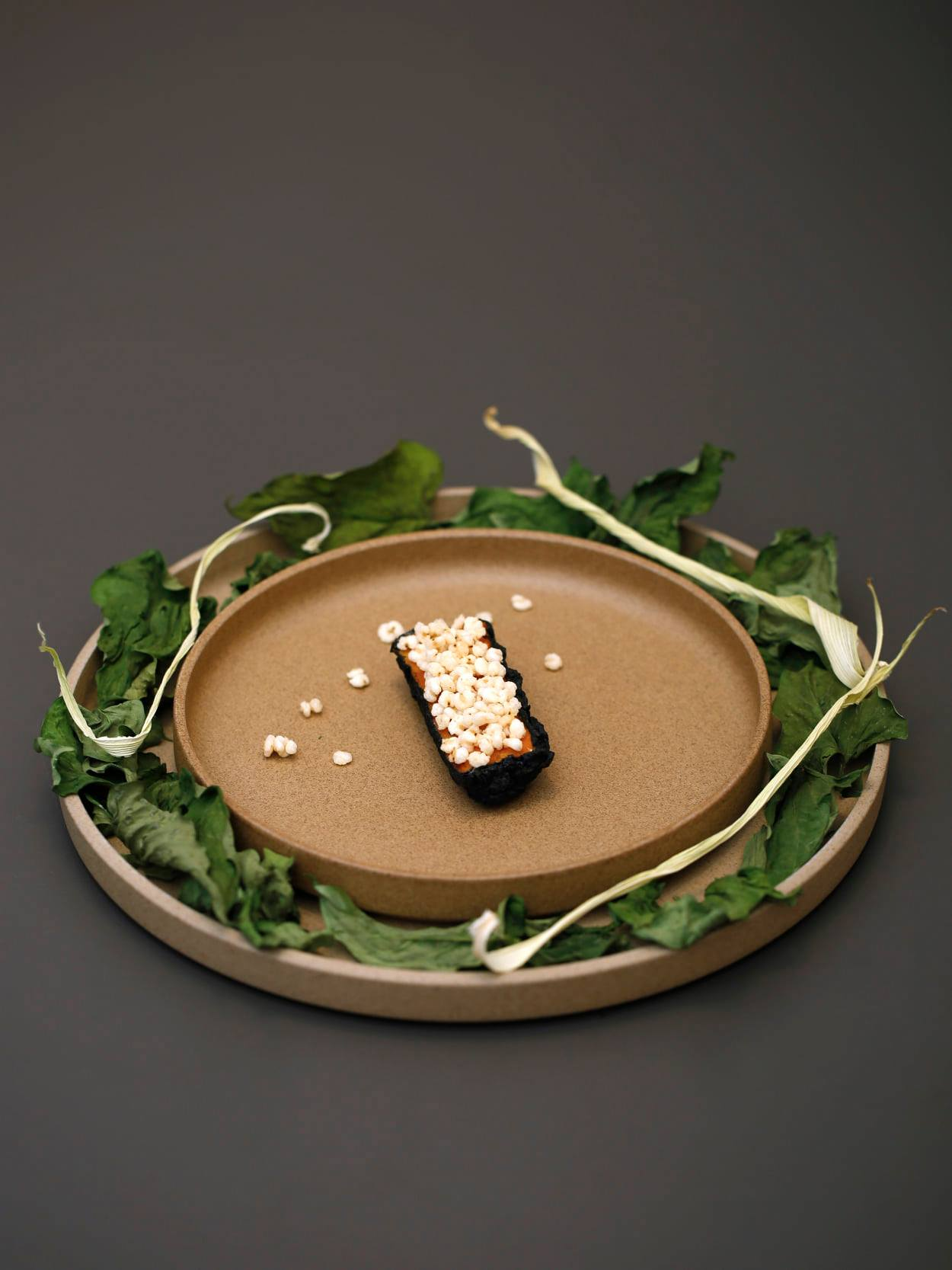 A piece of food, rectangular and topped with something resembling popcorn, at the center of a beige clay plate surrounded by leaves