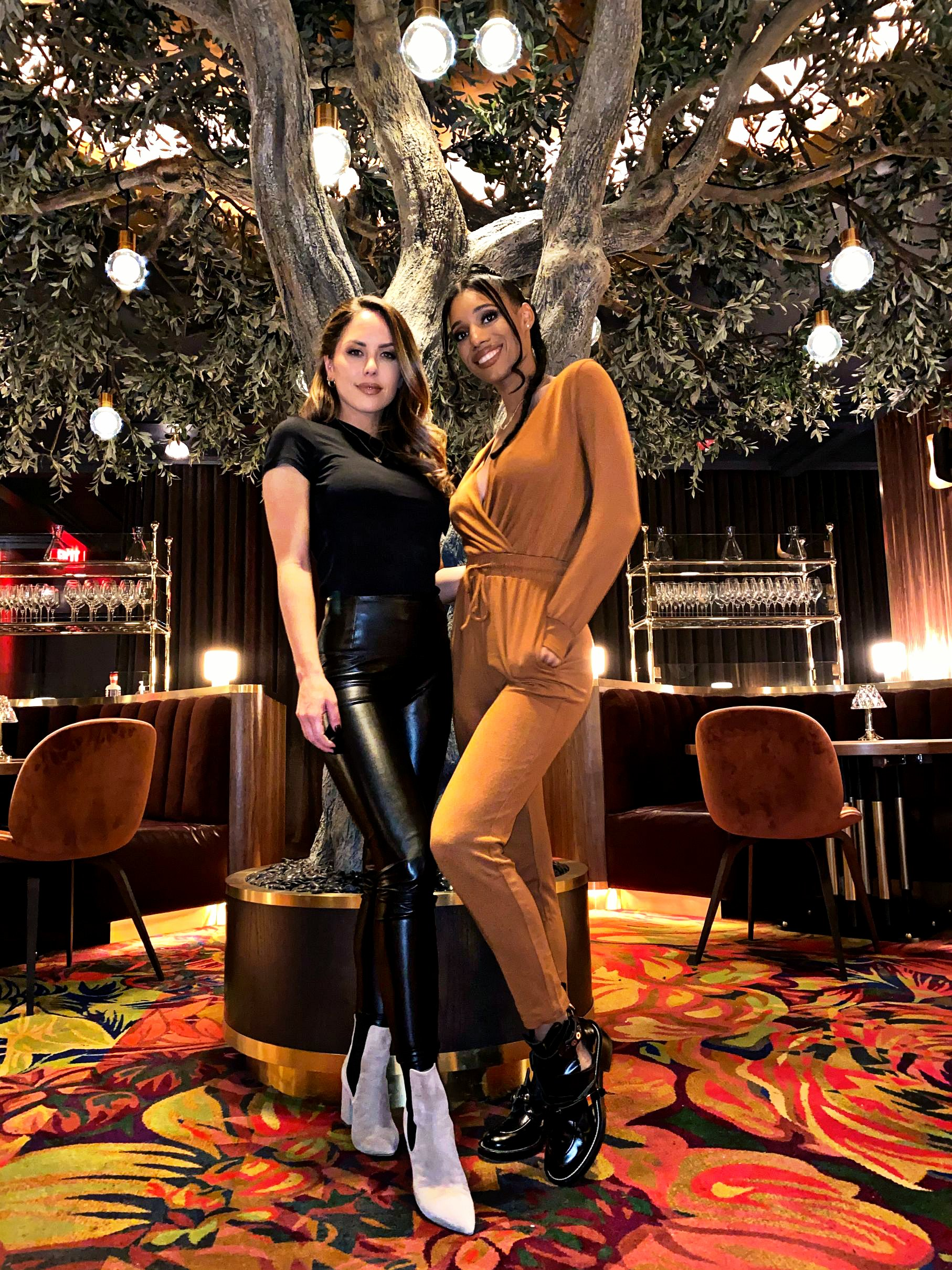 Two women stand in front of a tree in a dining room