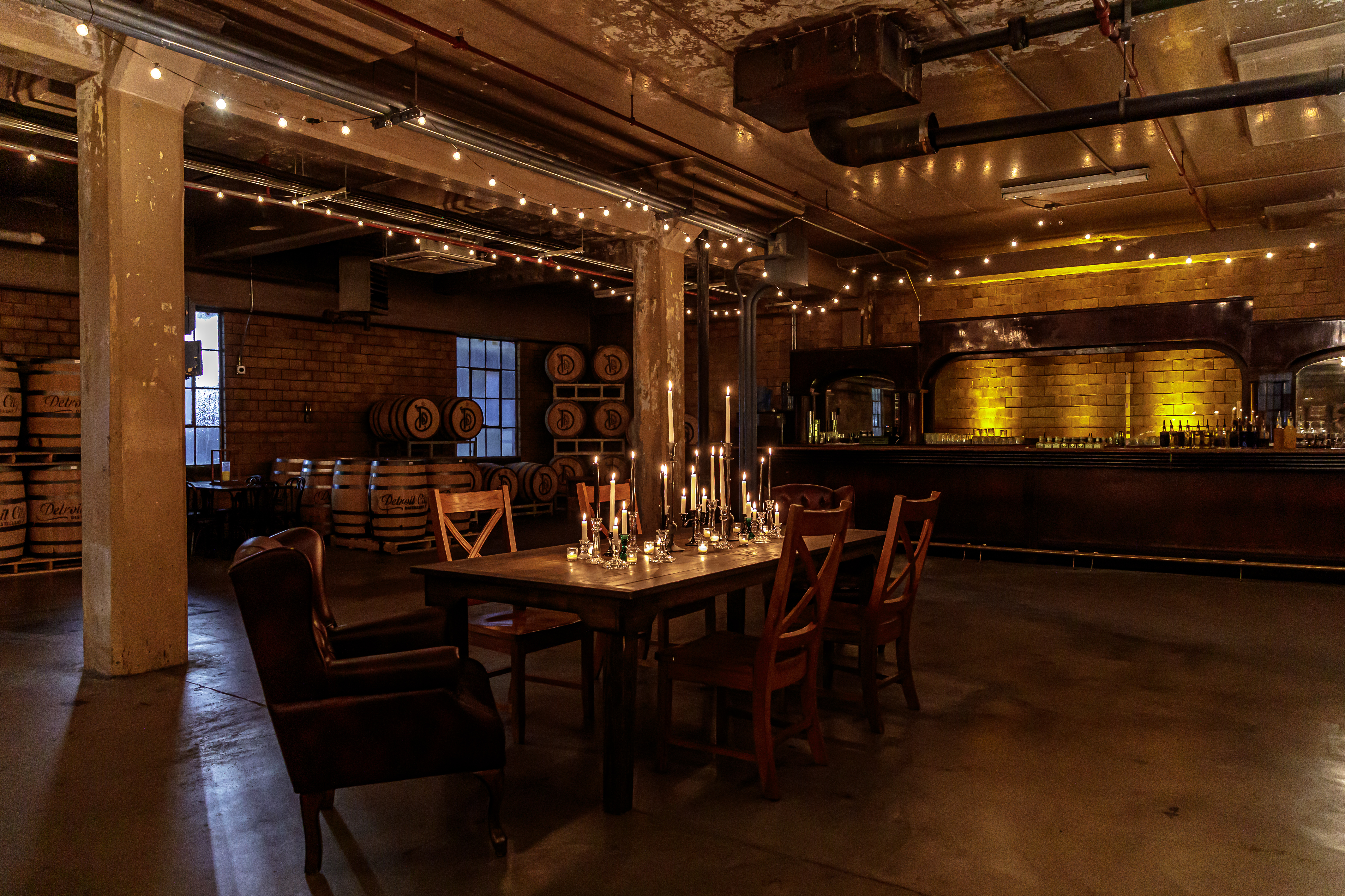 A table sits inside a dimly lit room with whiskey barrels, string lights, and candles.