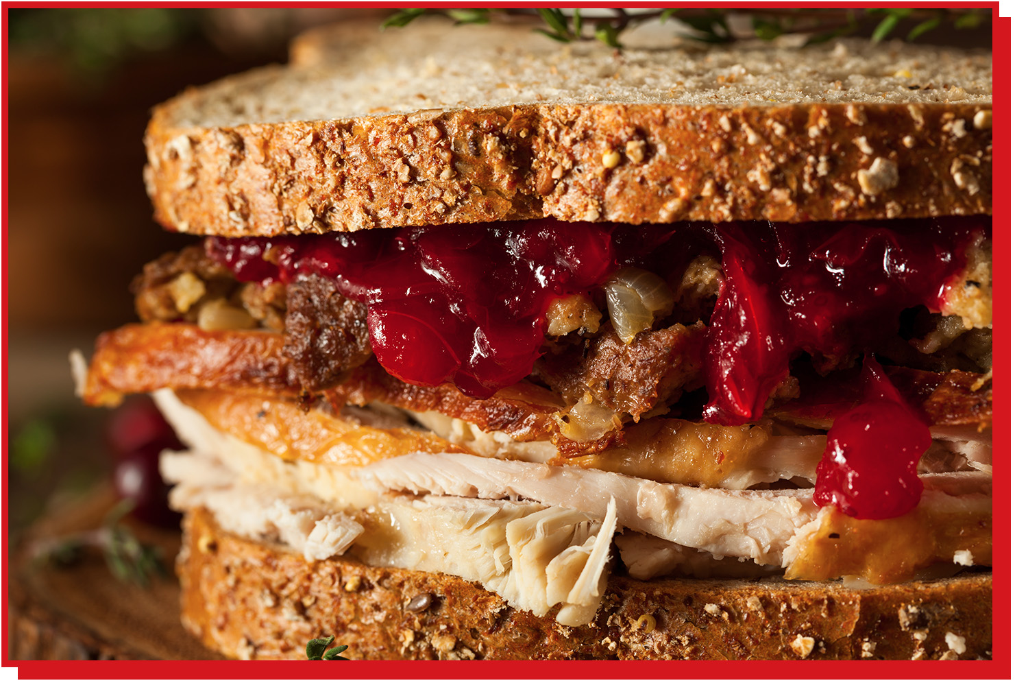 Sandwich with turkey, cranberry sauce, and stuffing in between two slices of bread.