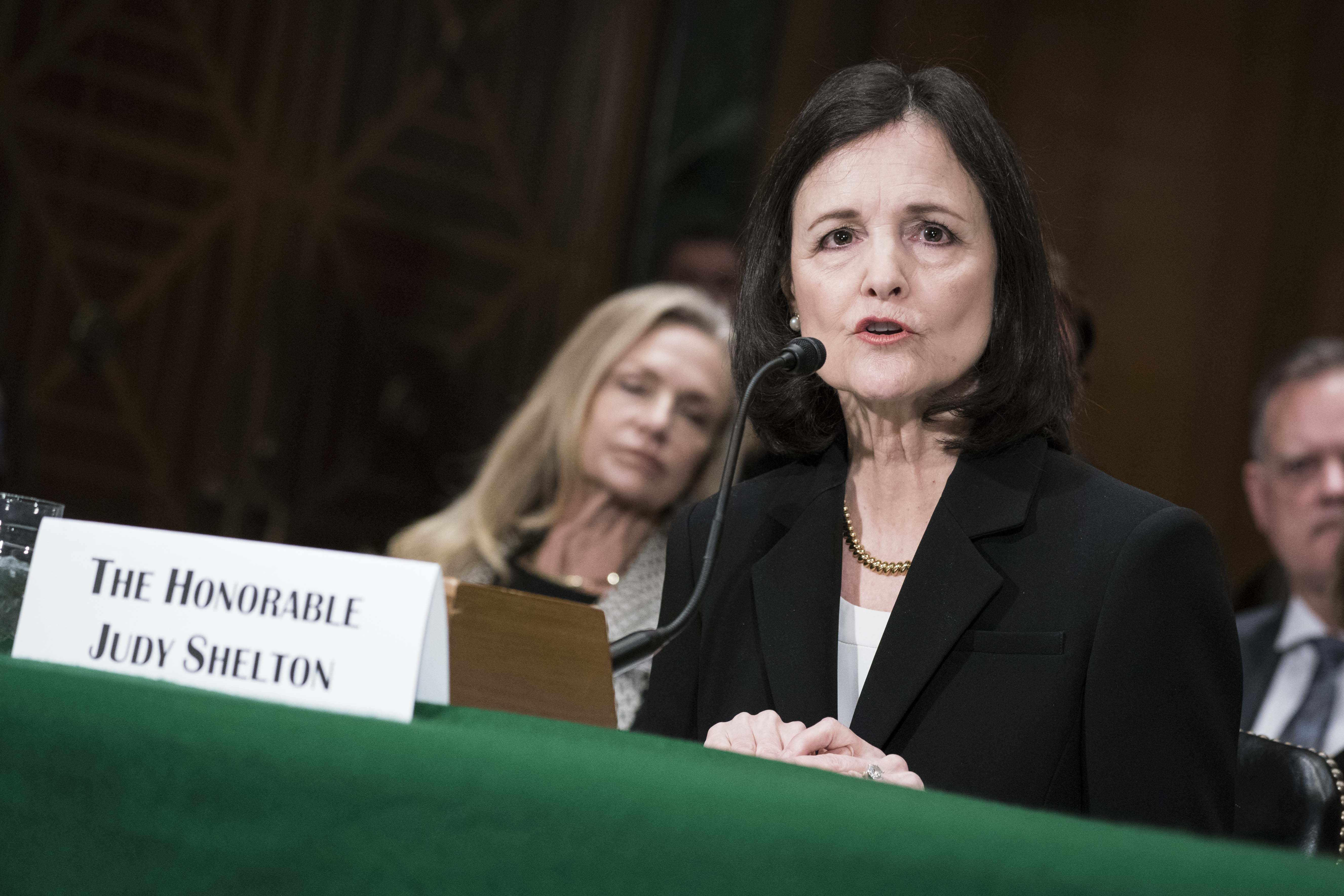 Judy Shelton speaks seated at a desk with a microphone.