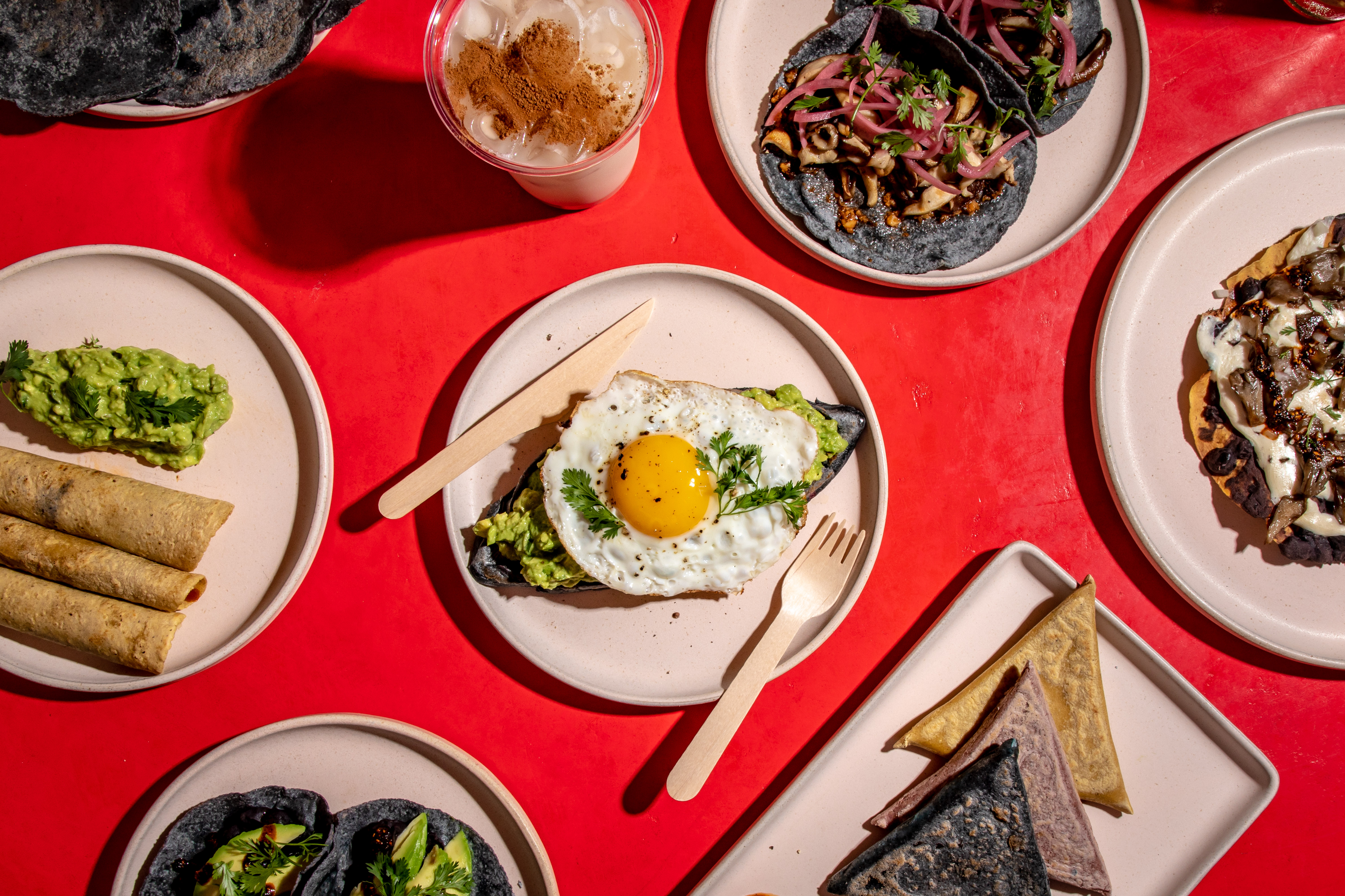 A sunny-side up fried egg sits over a memela with avocado in an overhead shot; the memela is surrounded by assorted dishes including tacos on blue corn tortillas and a cup of horchata