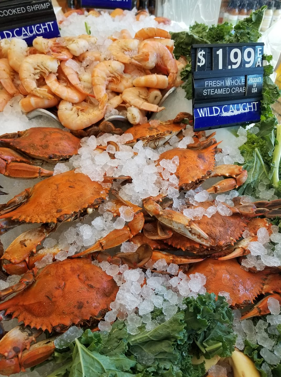 A bundle of wild caught red crabs and shrimp on ice in the cold case at seafood market Kathleen's Catch