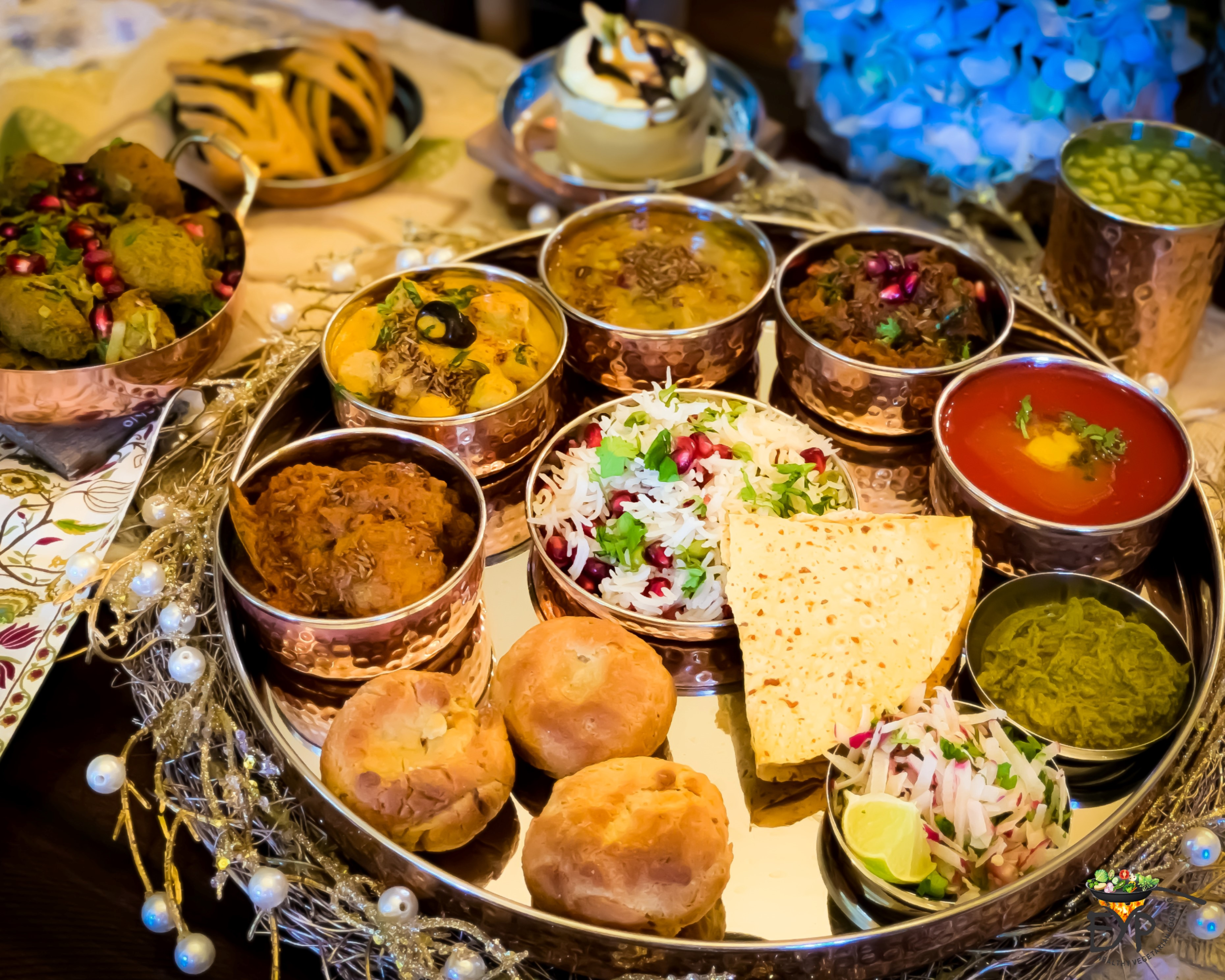 A large platter holding colorful small bowls of food and sauces, plus breads and rice