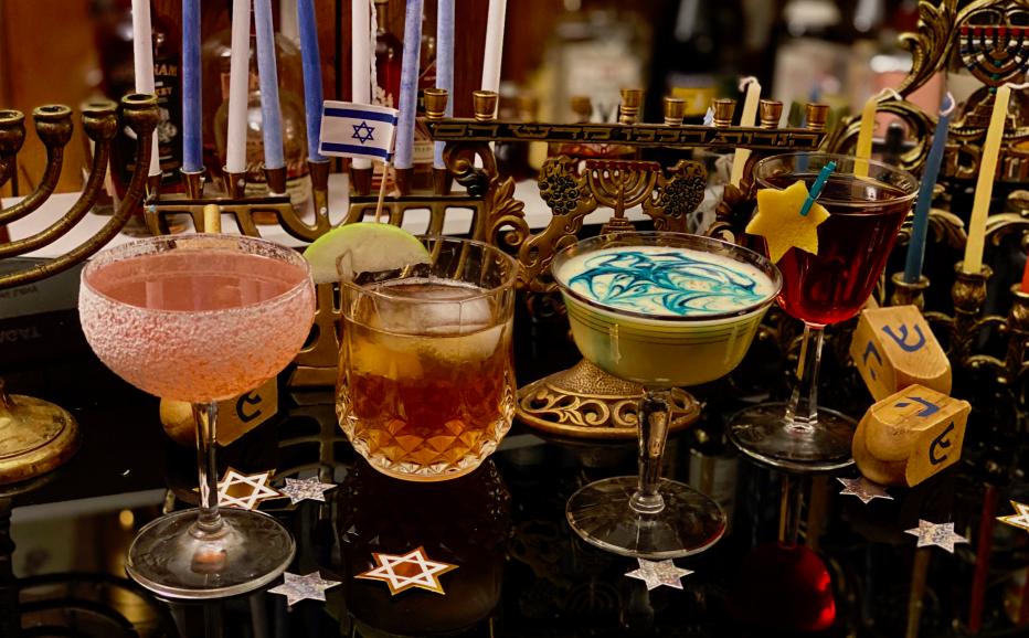 A lineup of Hanukkah-themed cocktails and Hanukkah paraphernalia, including a menorah and dreidels