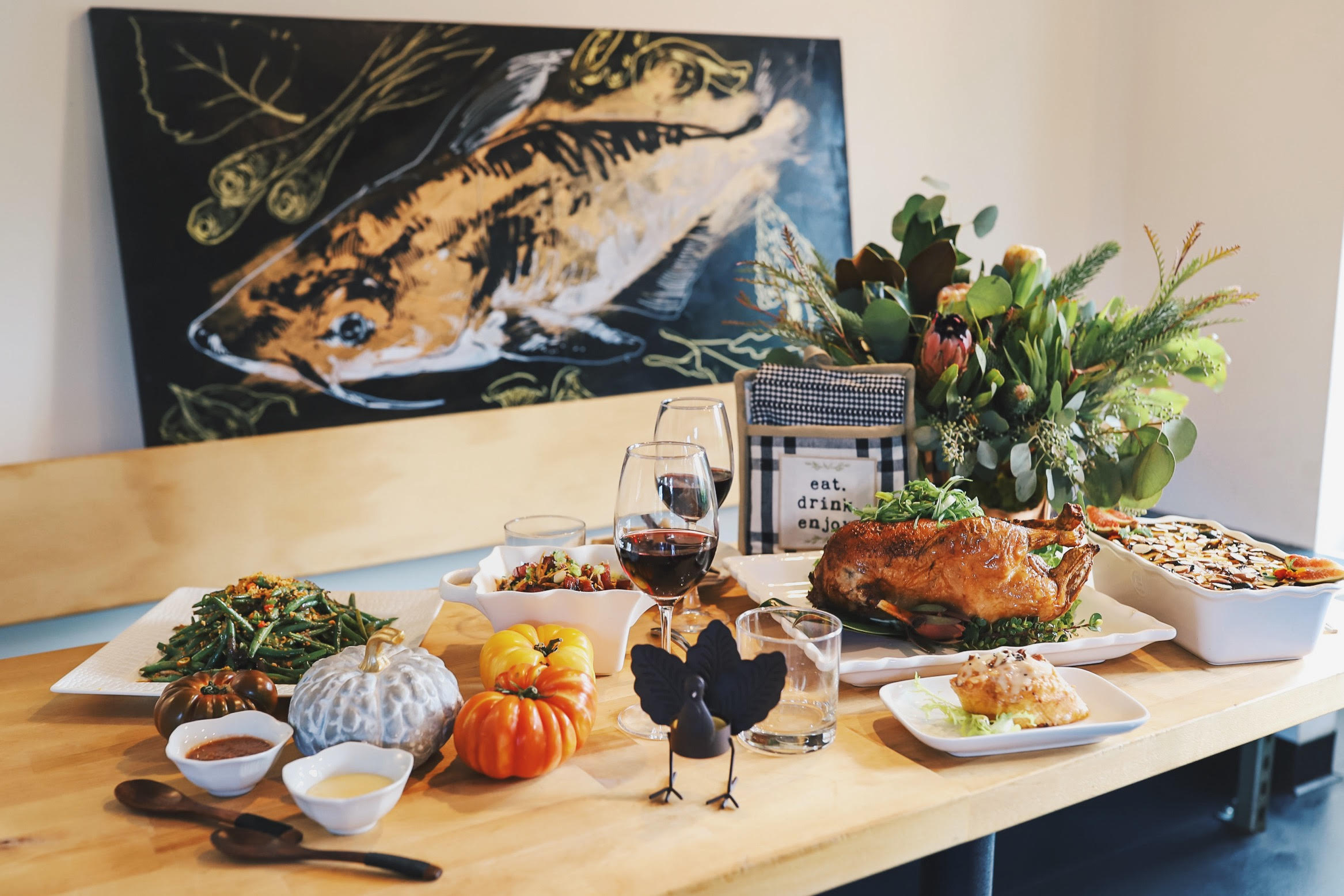 A table covered with a roasted duck, gourds, sauces in tureens, a turkey figurine, and two glasses of red wine, with a painting of a catfish in the background