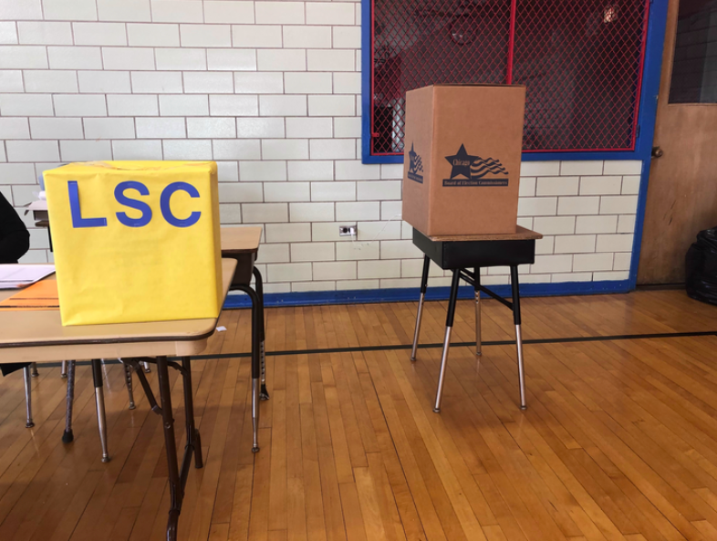 Two boxes for ballots stand in Yates Elementary in Chicago, a yellow box is for mail-in ballots dropped off at the campus and a brown box is for votes cast on site.
