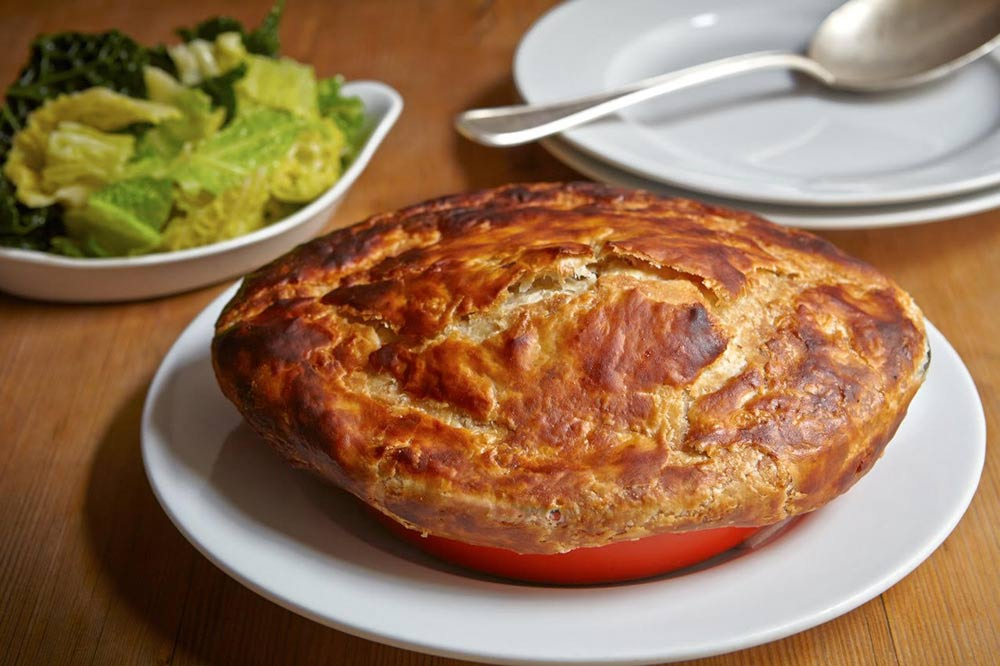 A beef pie in a ceramic dish, with buttered greens on a plate in the background