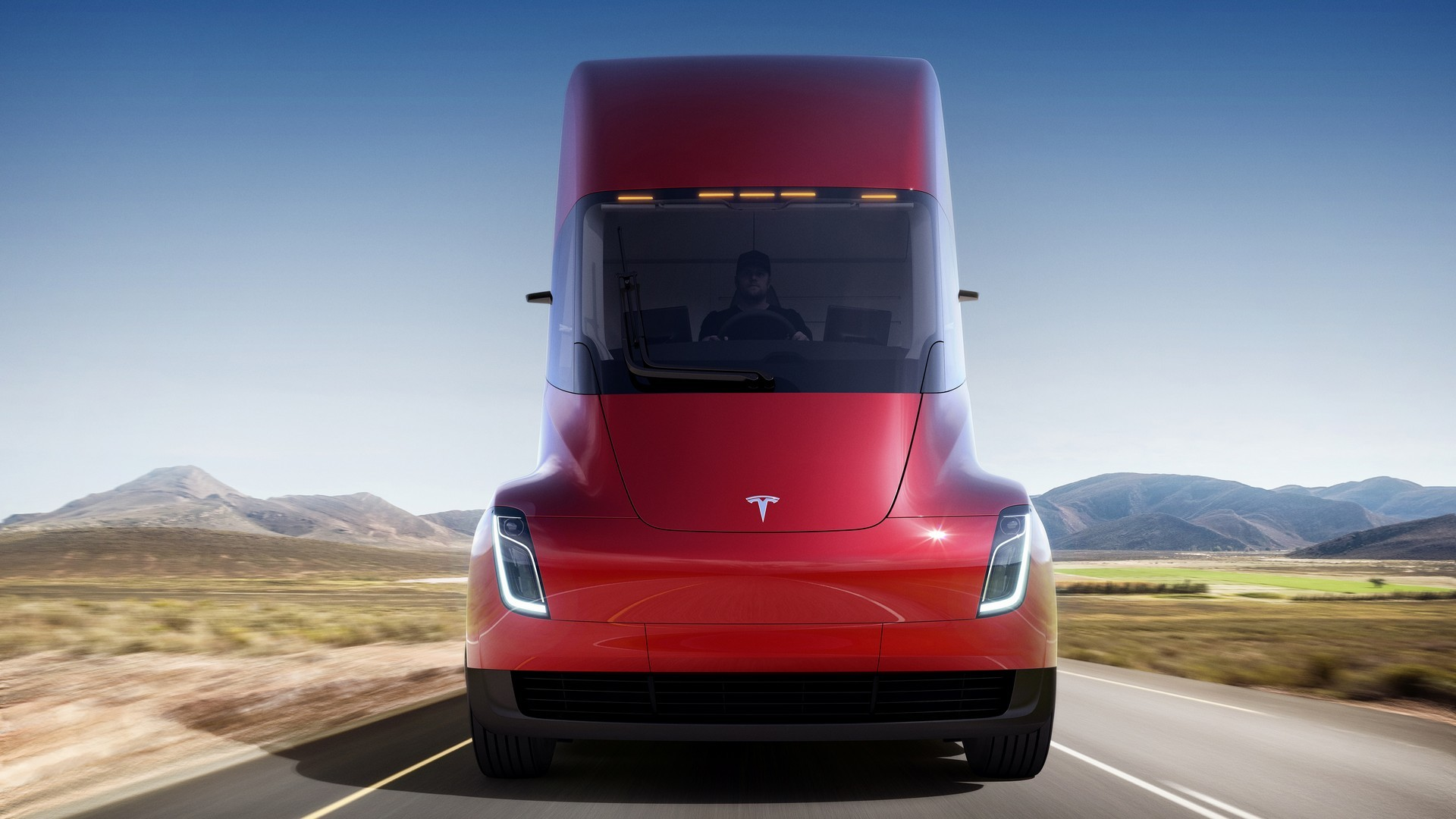 The front end of a Tesla semi driving down a deserted road toward the camera.