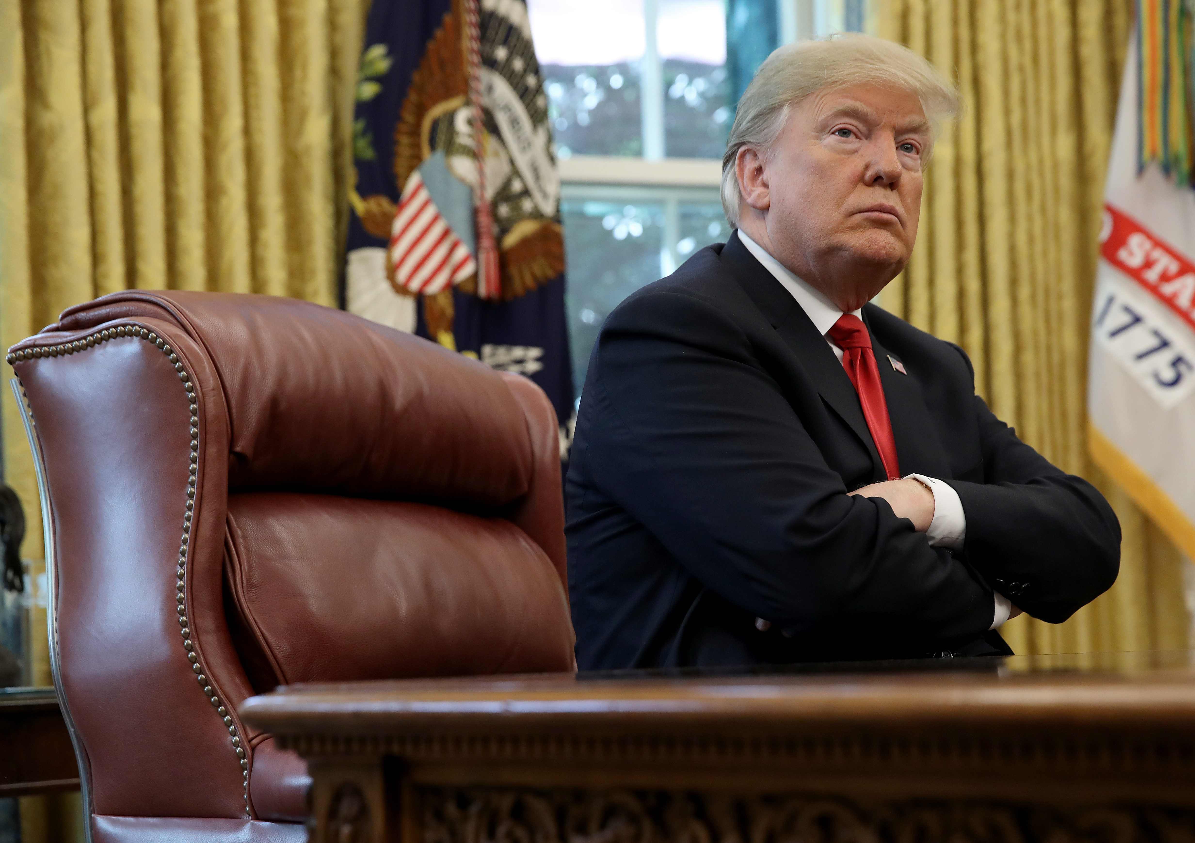 President Trump sitting with his arms crossed at his desk in the Oval Office of the White House.