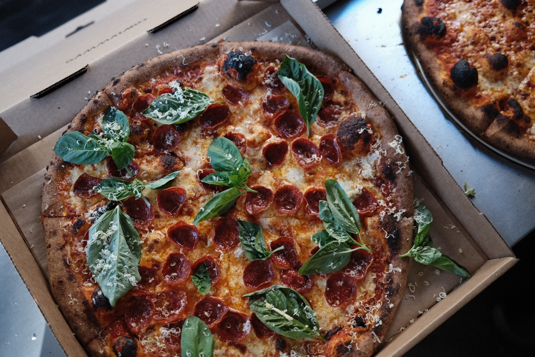 Pepperoni pizza with lots of basil in a cardboard pizza box