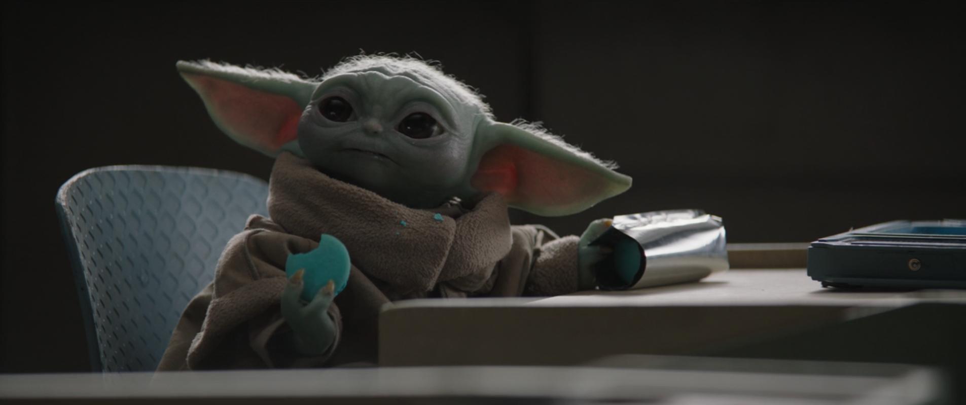 Baby Yoda enjoying a space macaroon in The Mandalorian