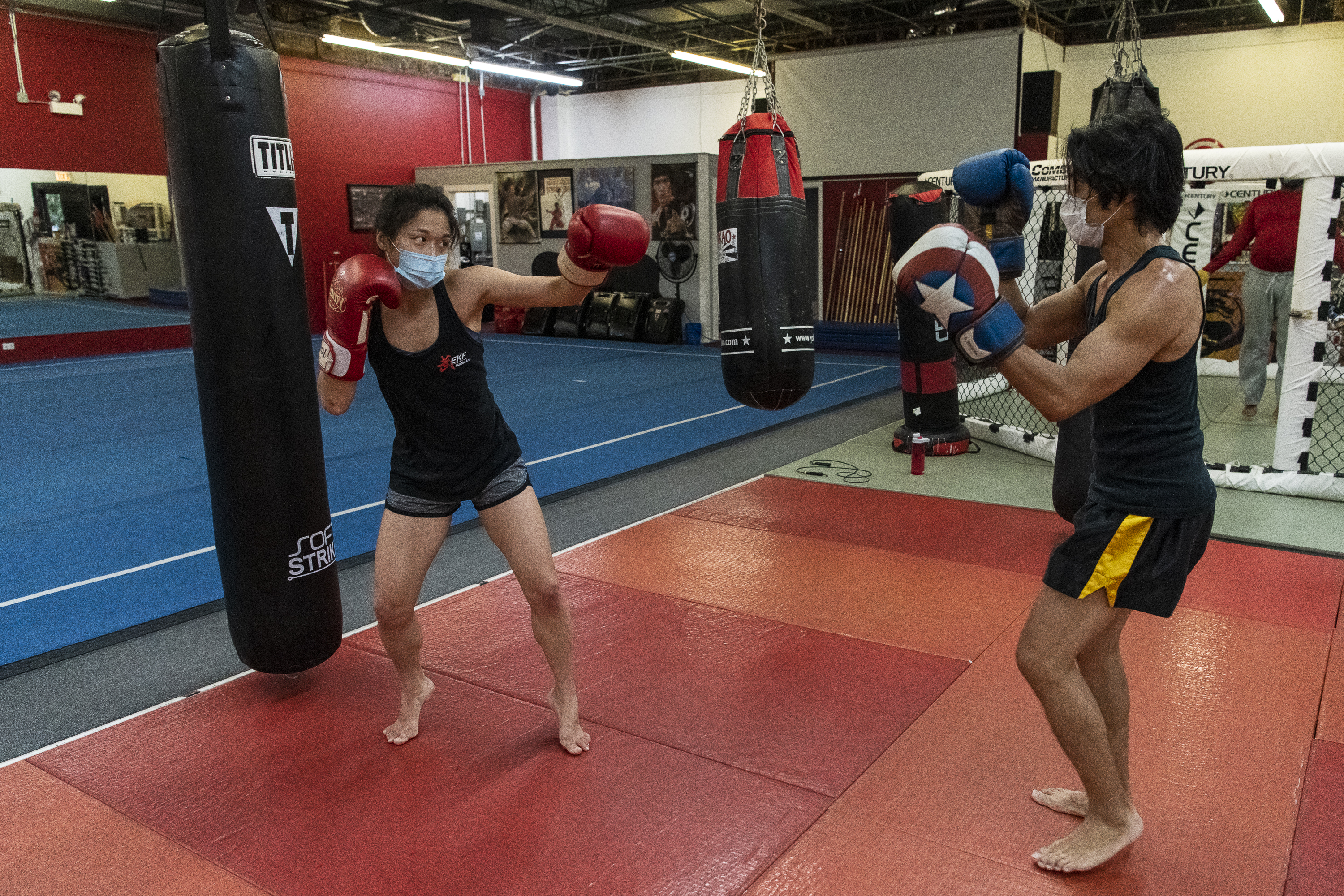 Jun Phan (left), a student at EKF Martial Arts spars with owner and head coach Tony Marquez during a boxing class in June. While group classes are no longer offered under new statewide restrictions, one-on-one classes are still allowed in gyms.