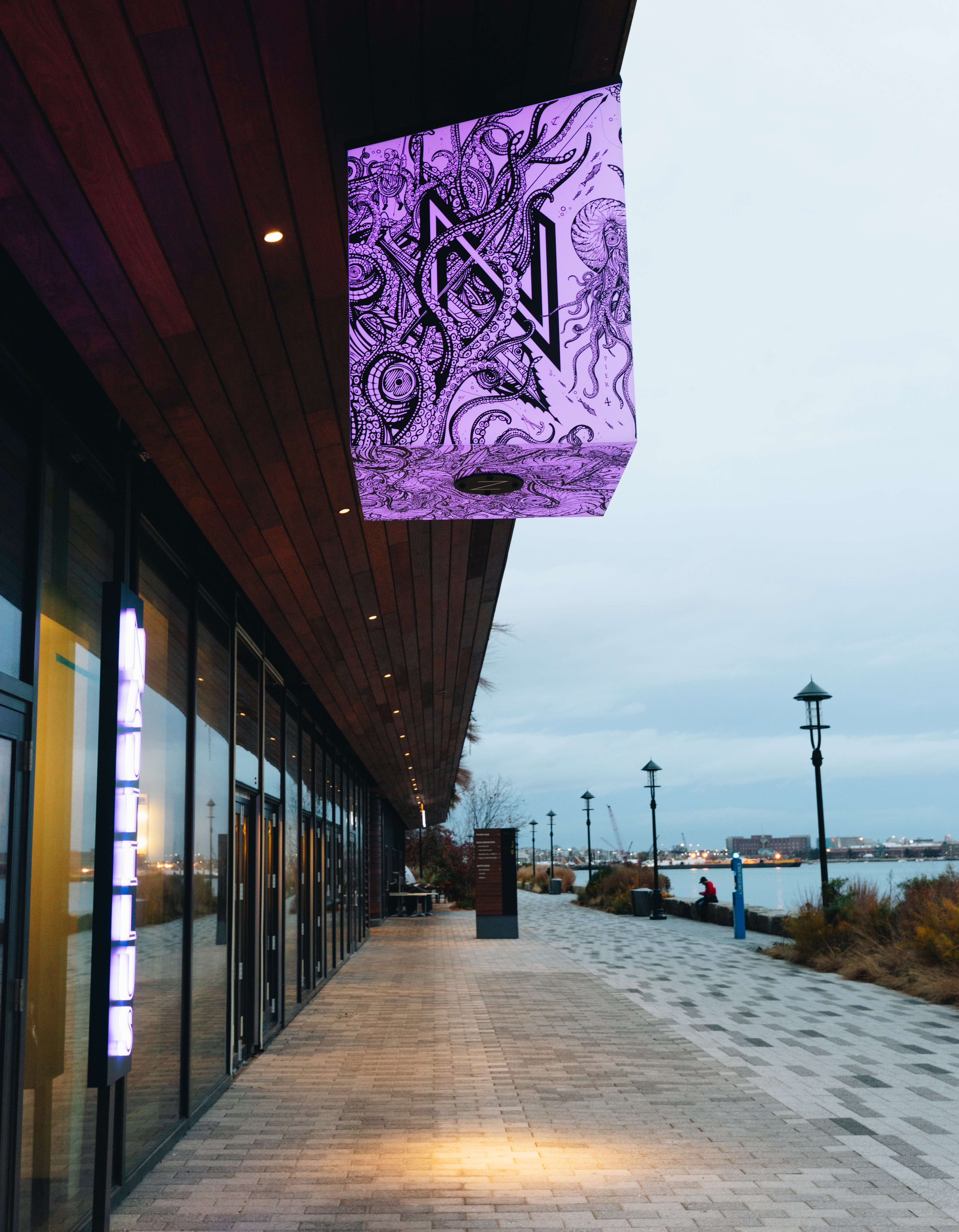 """Light purple signage features a black letter """"N"""" surrounded by an intricate nautical pattern of octopus tentacles. It hangs on the awning of a modern-looking waterfront building."""