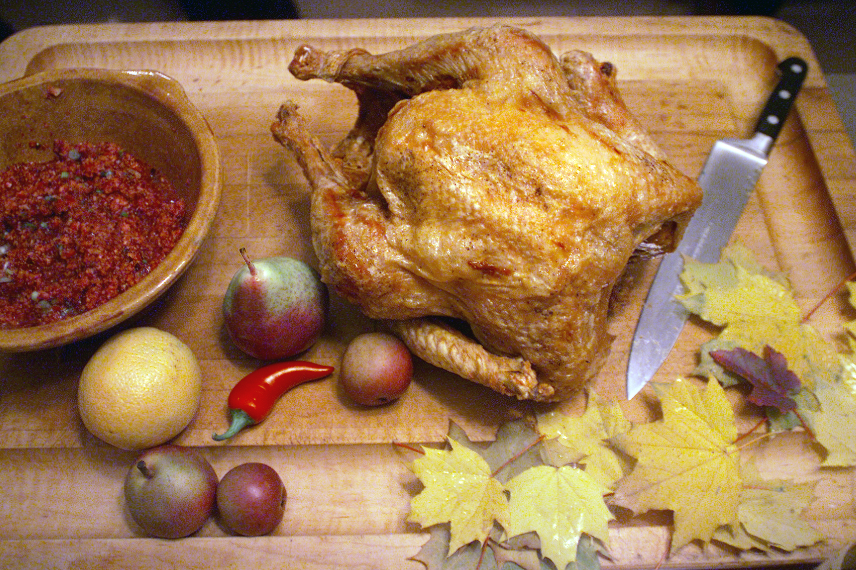 A turkey sits on a cutting board next to a knife, leaves, fruits and vegetables, and stuffing.