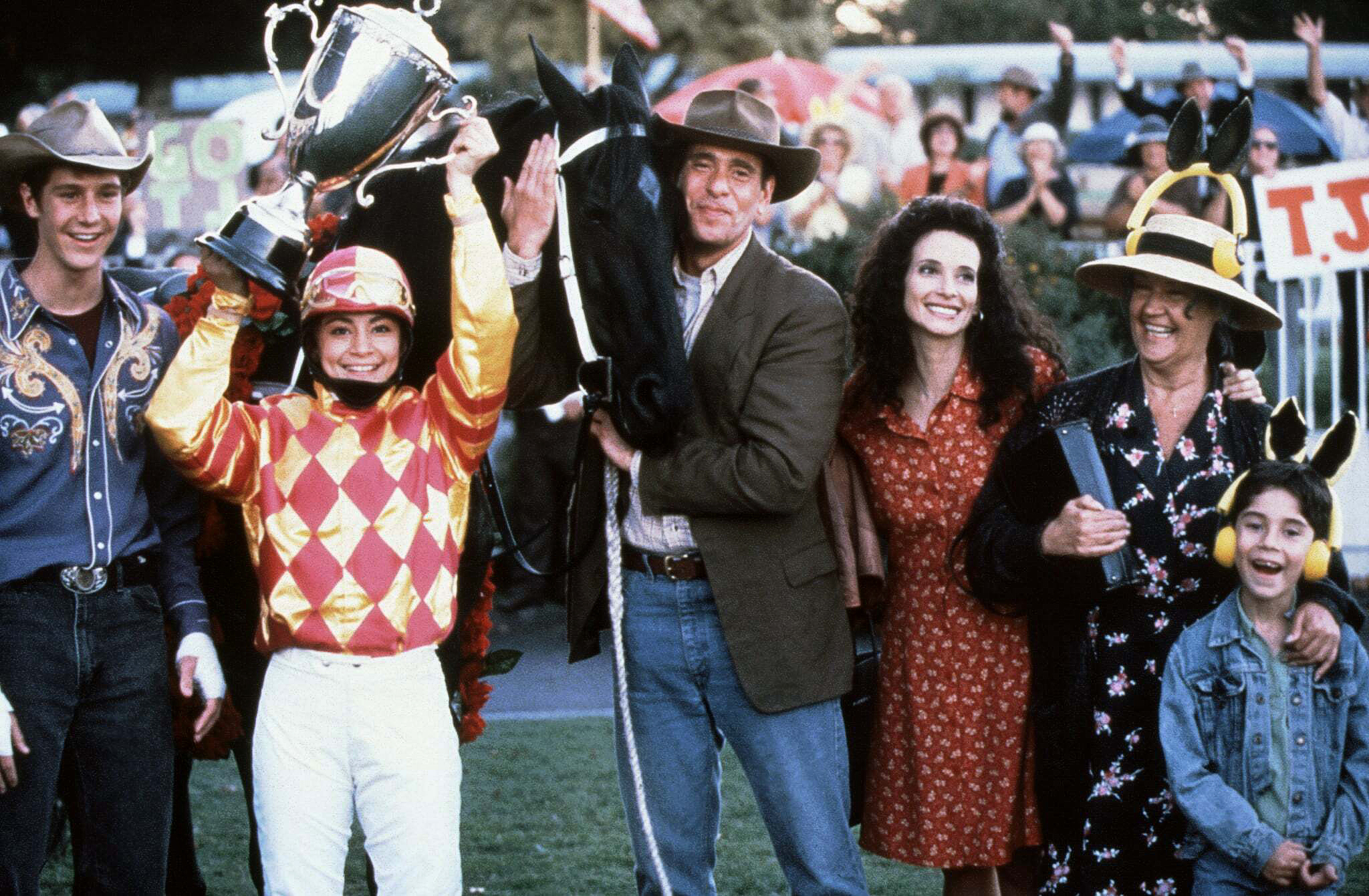 Jockey and her horse with a group of people celebrating a win.