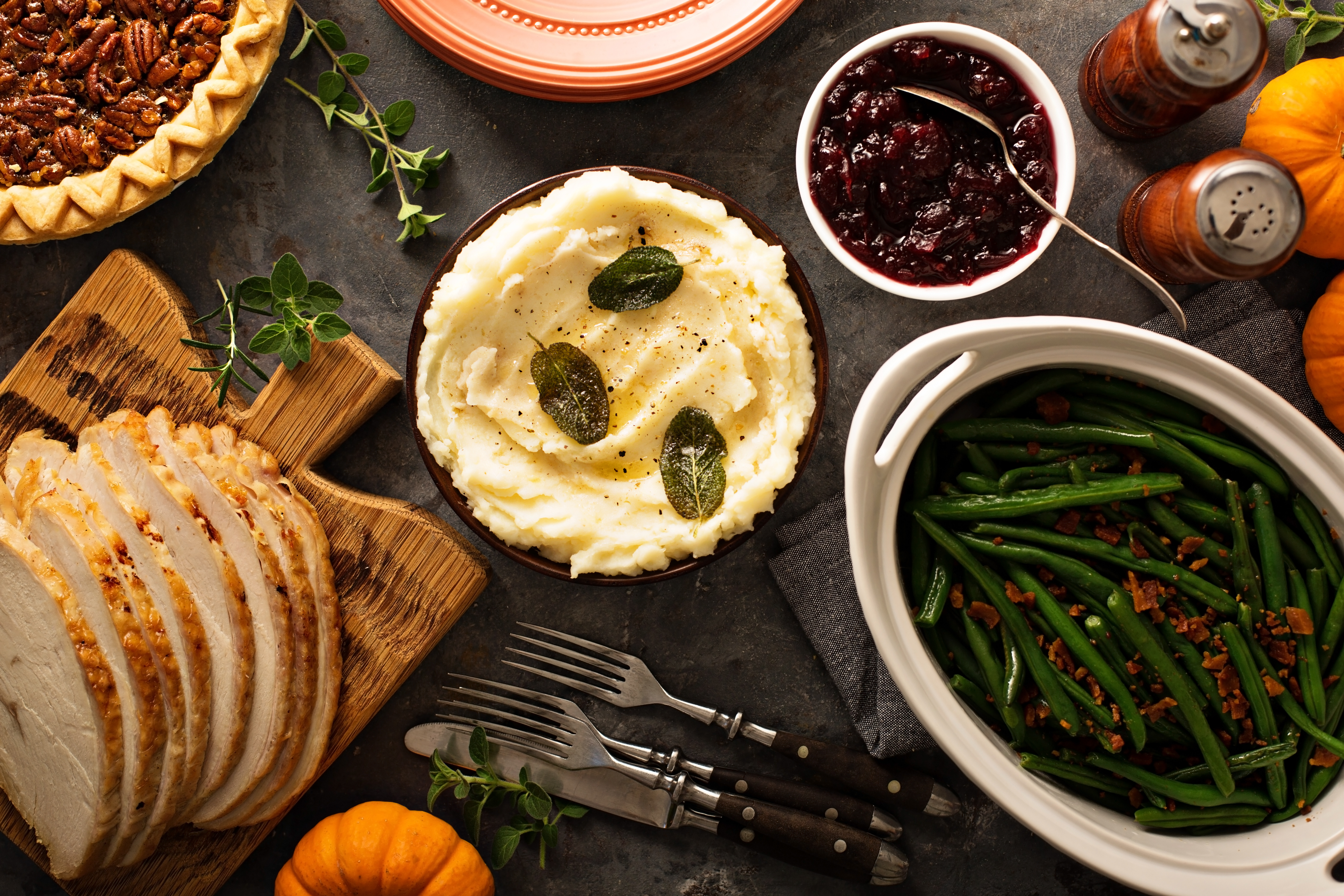 Bowls of green beans, cranberry sauce, and mashed potatoes, a plate of sliced roasted turkey, and a pecan pie on a black table, photographed from above.
