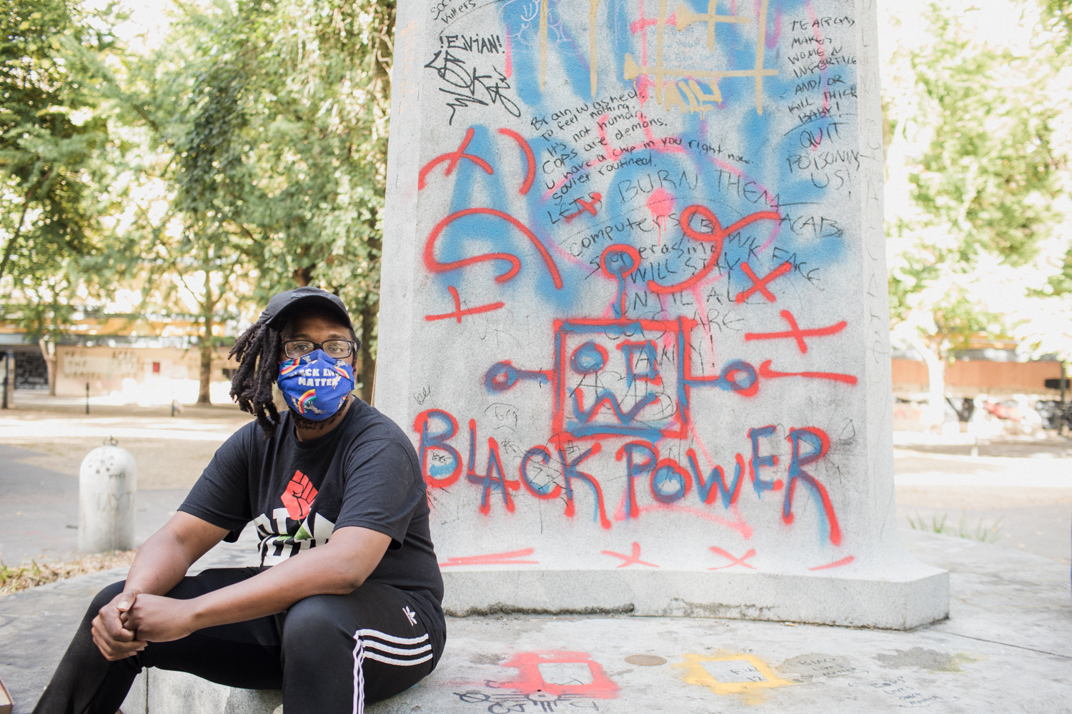 """A man sits by a monument with """"Black Power"""" spraypainted on it"""